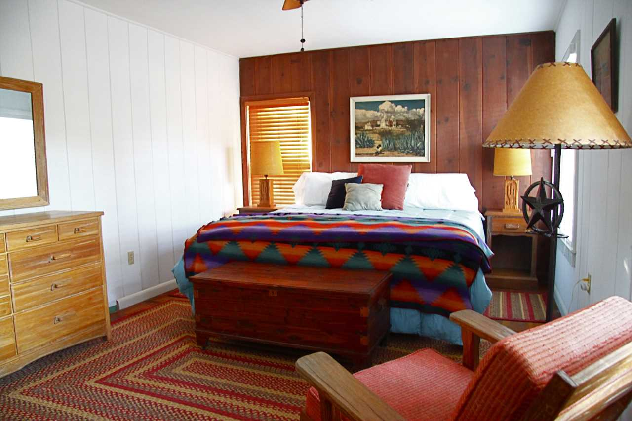 The comfy master bedroom features a wood accent wall and a great big king-sized bed. Additionally, clean bed and bath linens are provided for all.