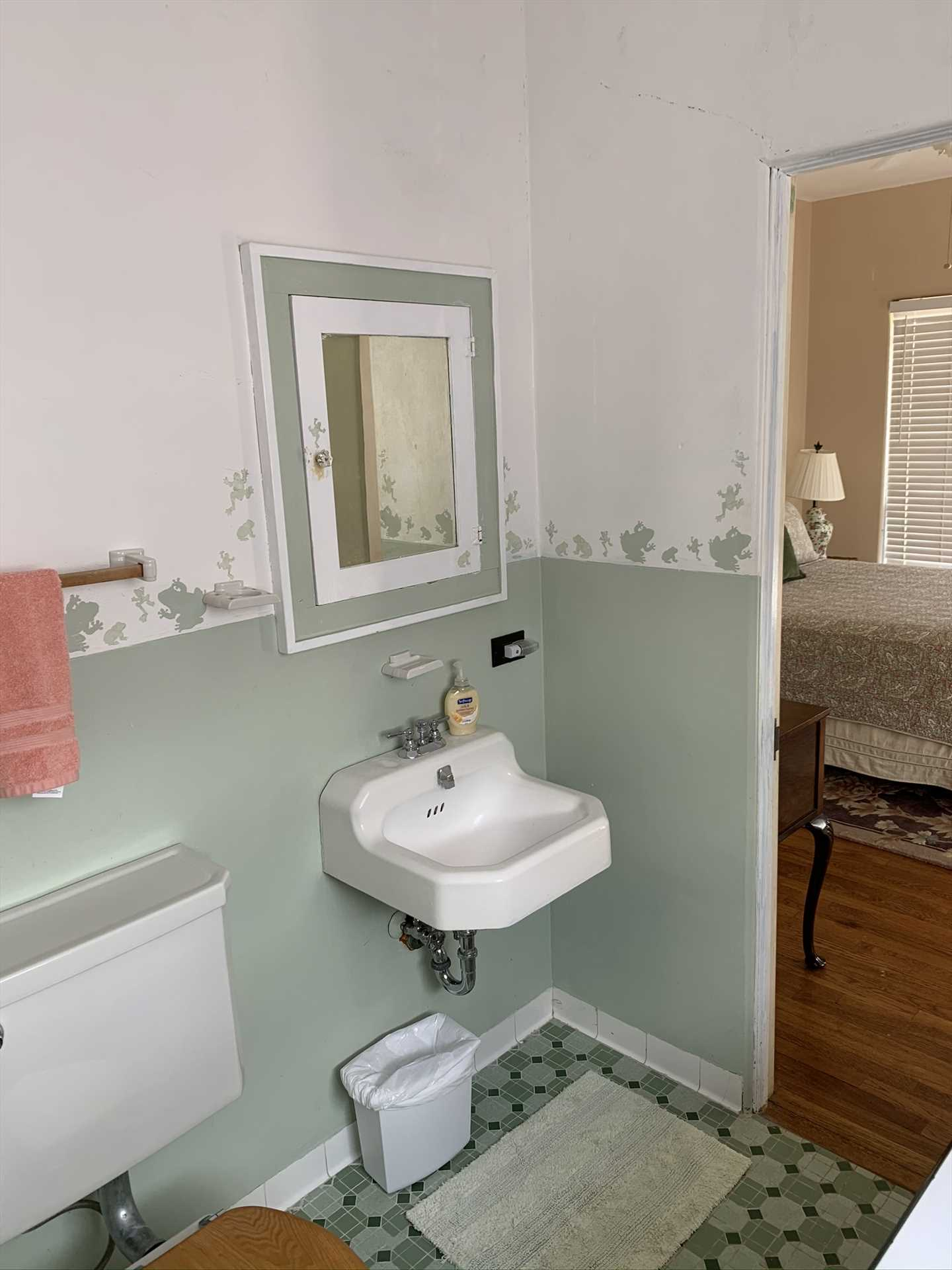 The master and second bedrooms upstairs share this colorful Jack & Jill bath, which is fully equipped with a shower.