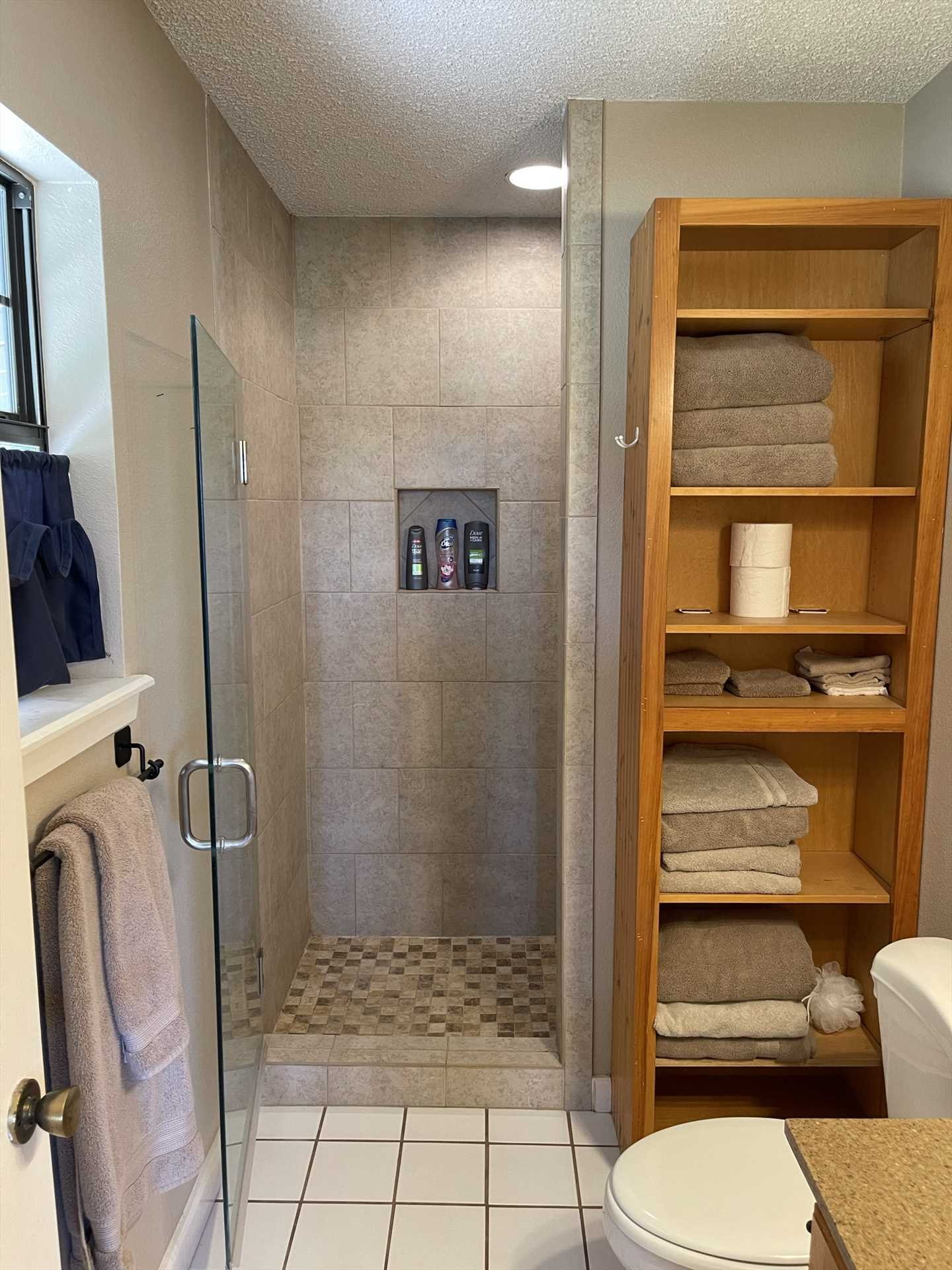 The sparkling-clean master bath features a nice glass-door step-in shower.