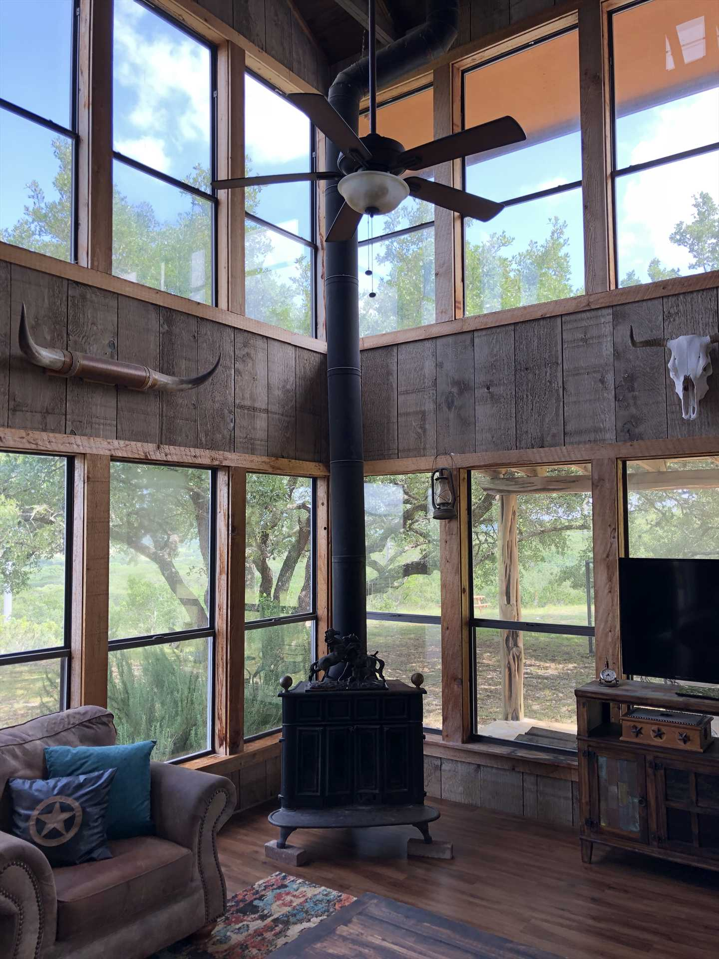 The two-story-tall living area invites tons of natural light into the rustic space, and views of the Hill Country that have to be seen to be believed.