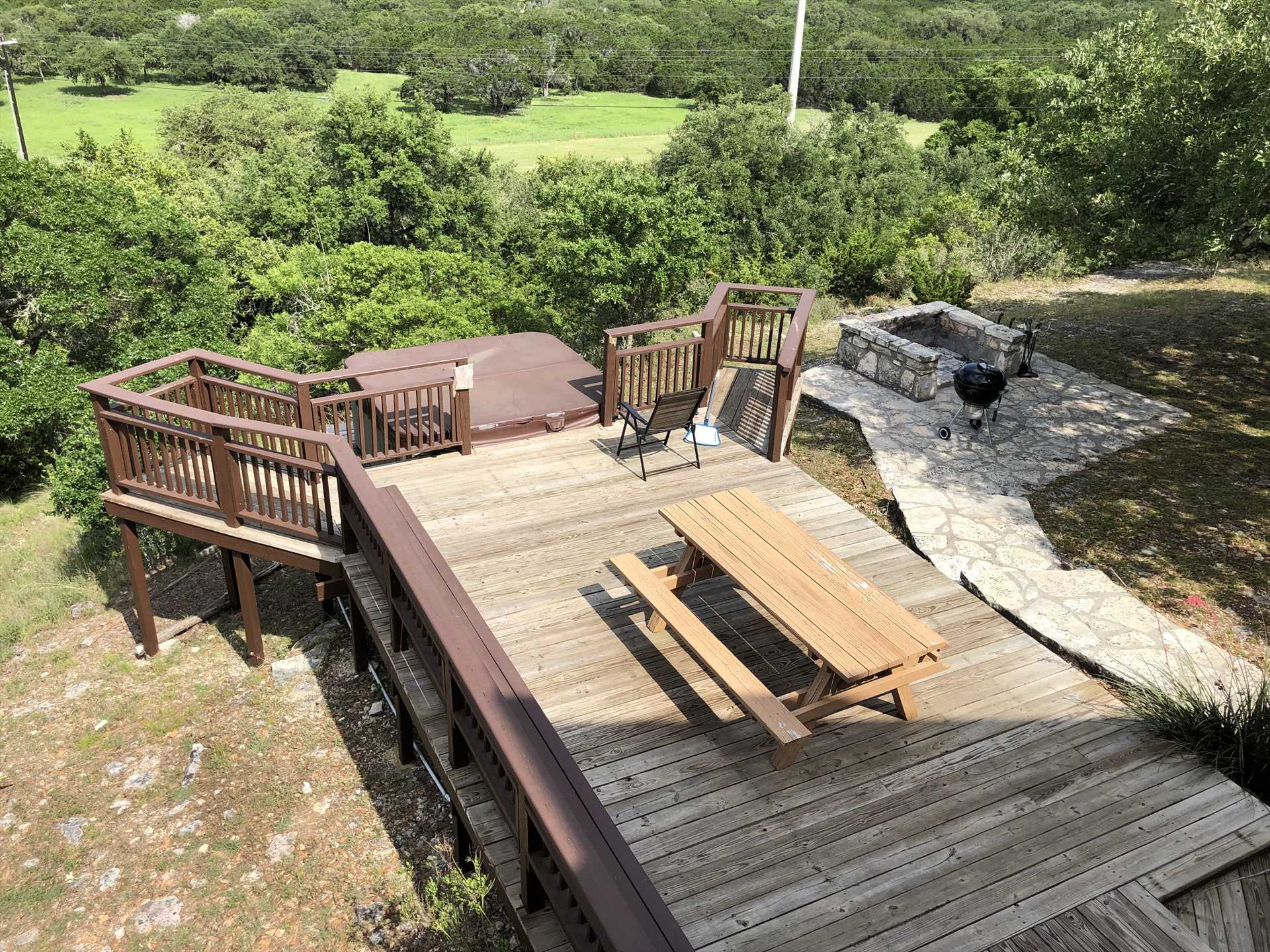 Let's see...fire pit, charcoal grill, plenty of seating, a hot tub, and eye-popping Hill Country views. You may never want to leave the deck!