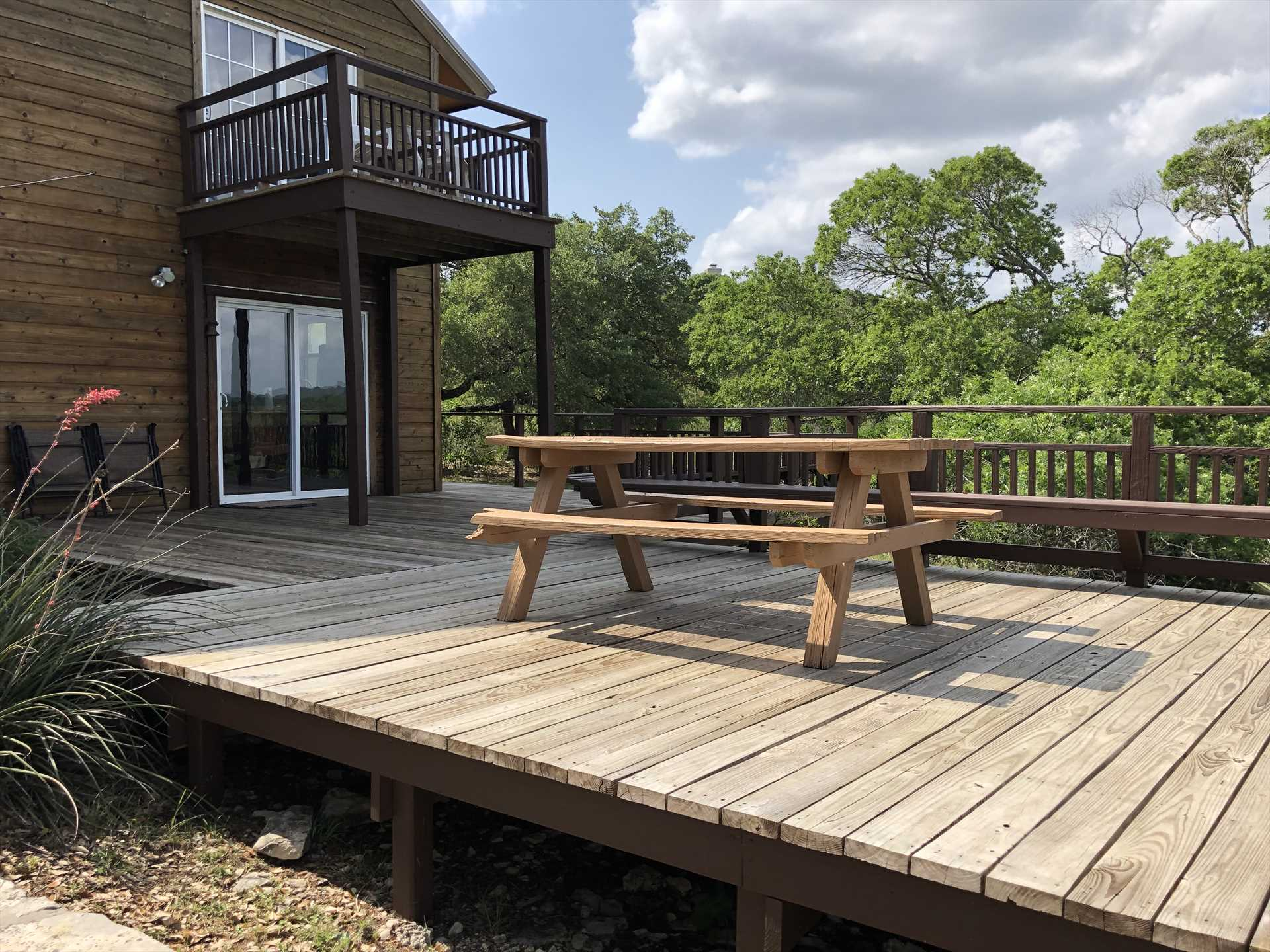 The upper level of the back deck features a picnic table and bench-style seating. Just a few steps down from here is your private hot tub!