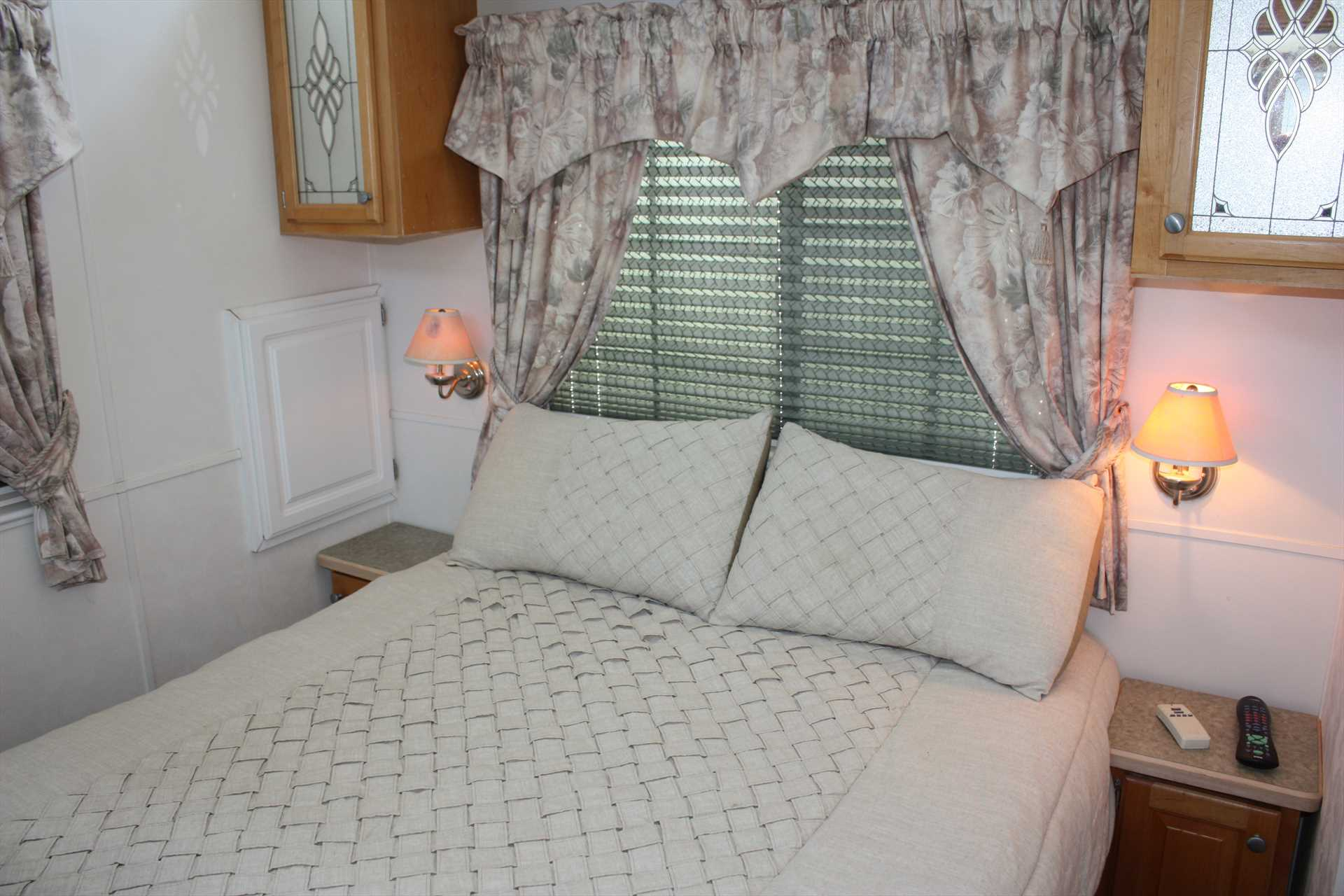 The charming bedroom here features a plush and restful queen-sized bed, and clean and fresh bed and bath linens are provided.