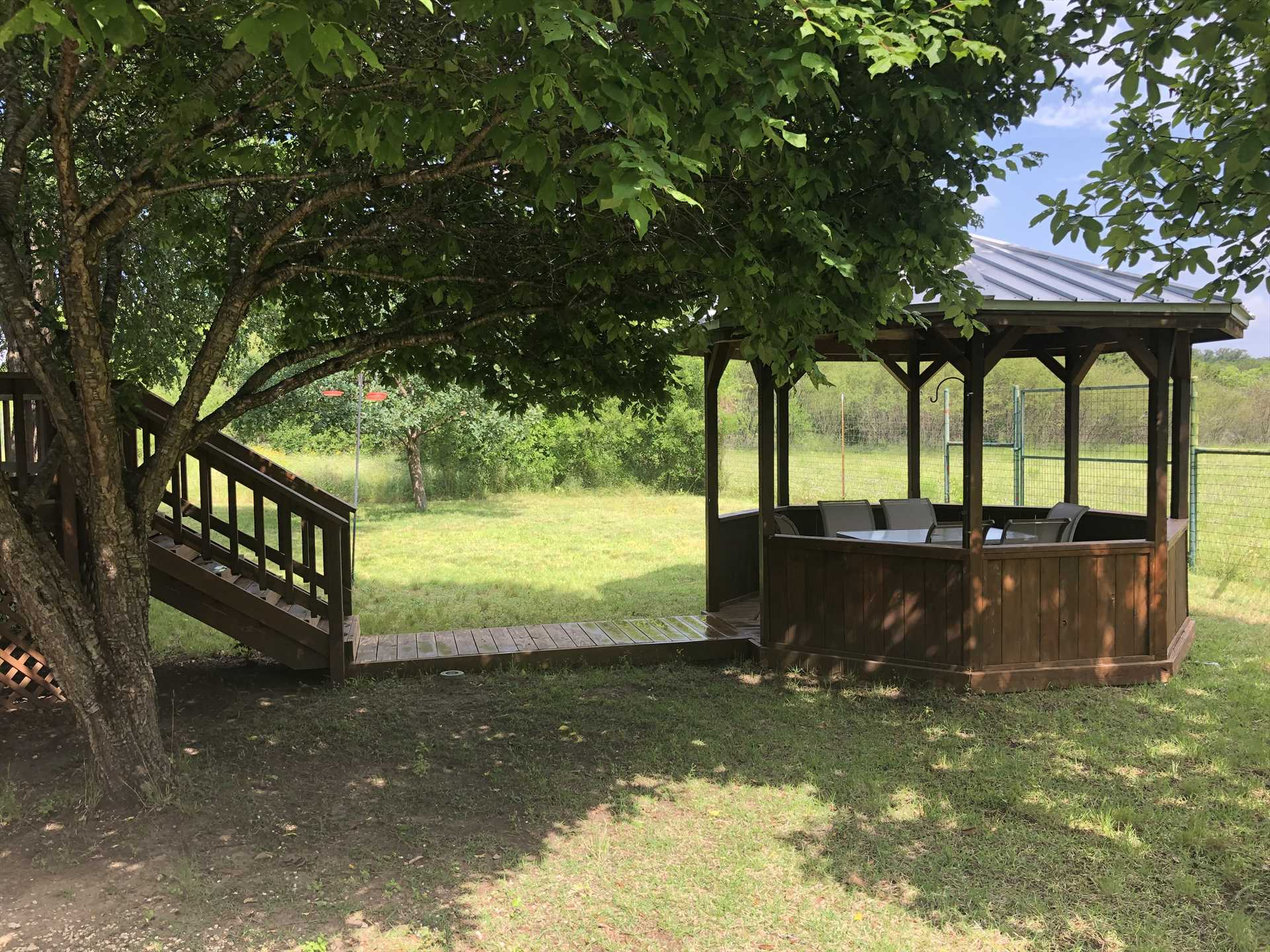 The open-air gazebo has outdoor furniture, so everyone can relax under the shade of its peaked roof. It's a great place to enjoy a meal prepared on the gas grill!