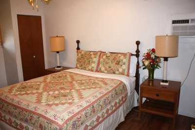 In the second bedroom, a plush queen-sized bed awaits, tastefully draped in warm and clean linens.