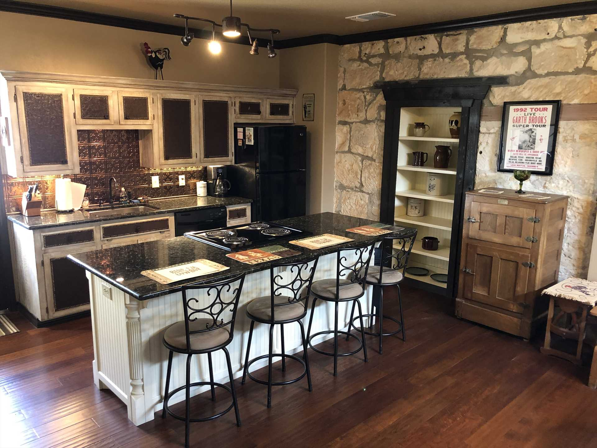 The full kitchen features not only modern appliances, but all the cooking ware, utensils, glasses, and serving ware you'll need. There's also a sweet-looking bar area with seating for four!