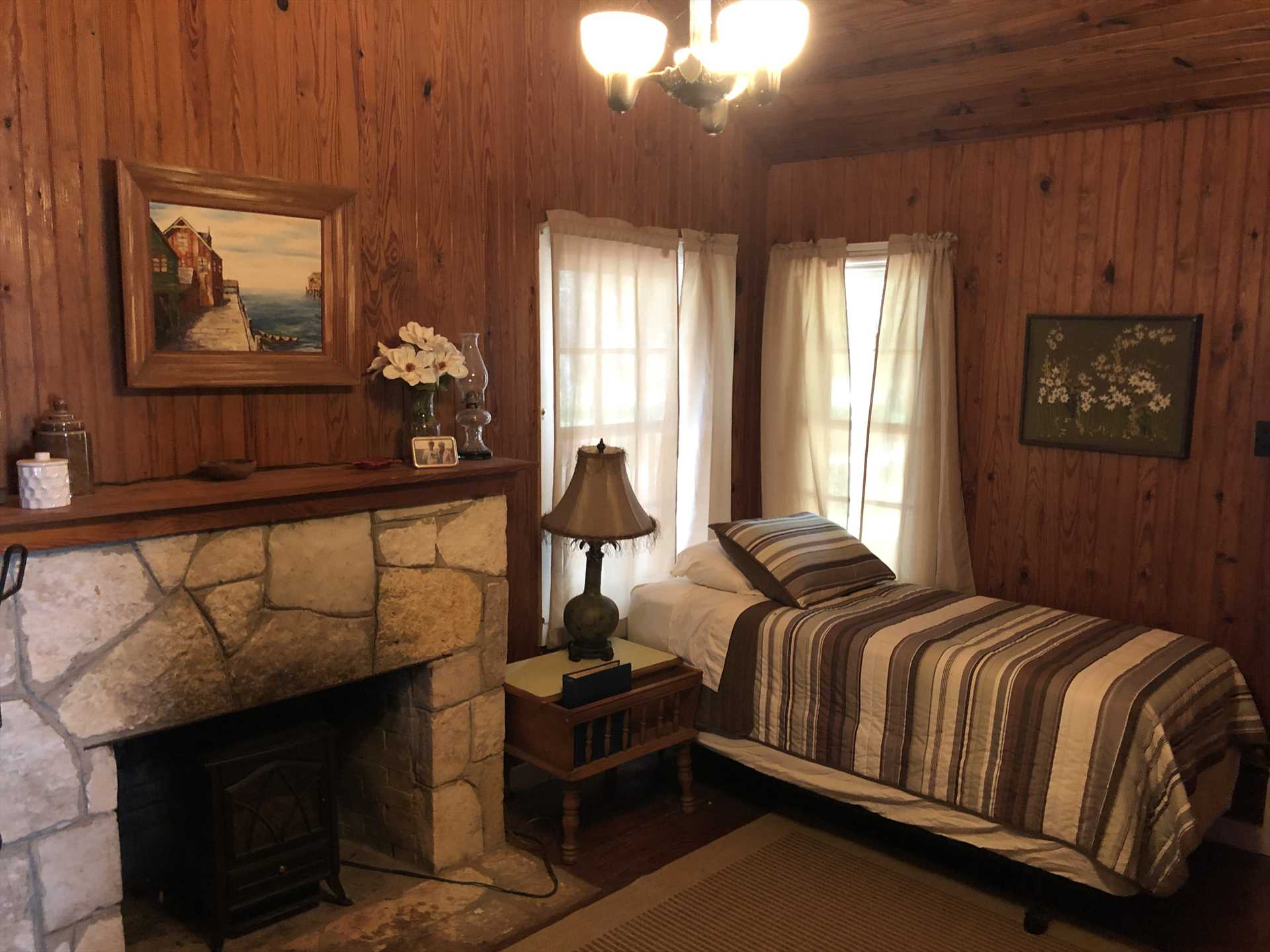 The twin bed in the den is close to the electric fireplace-a great place to warm your toes on chilly nights!