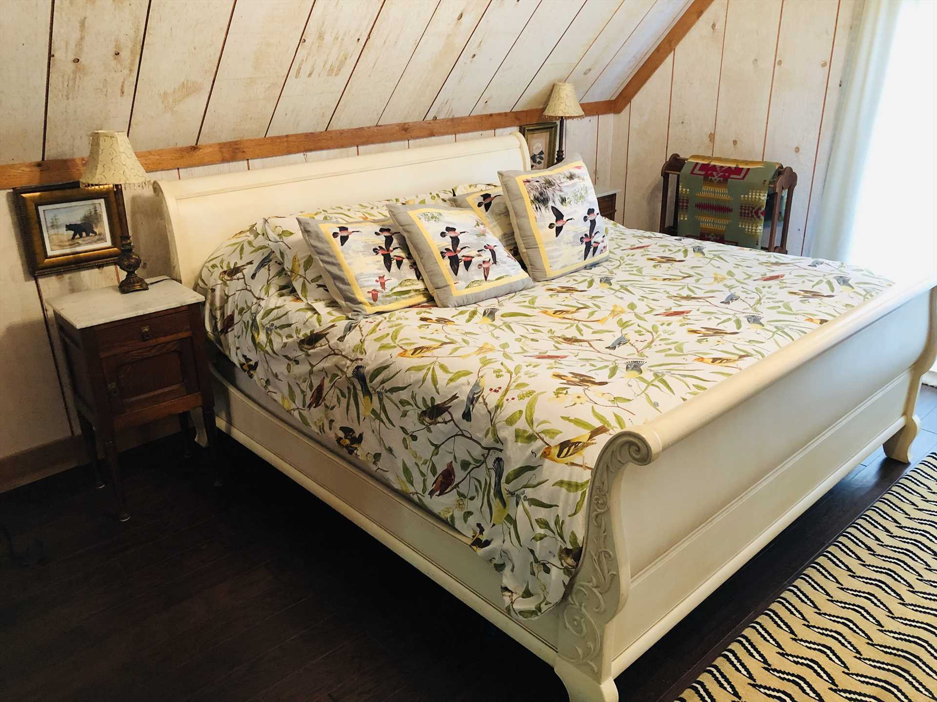 The vintage sleigh-style bed is fully dressed with soft, quality linens and throw pillows.