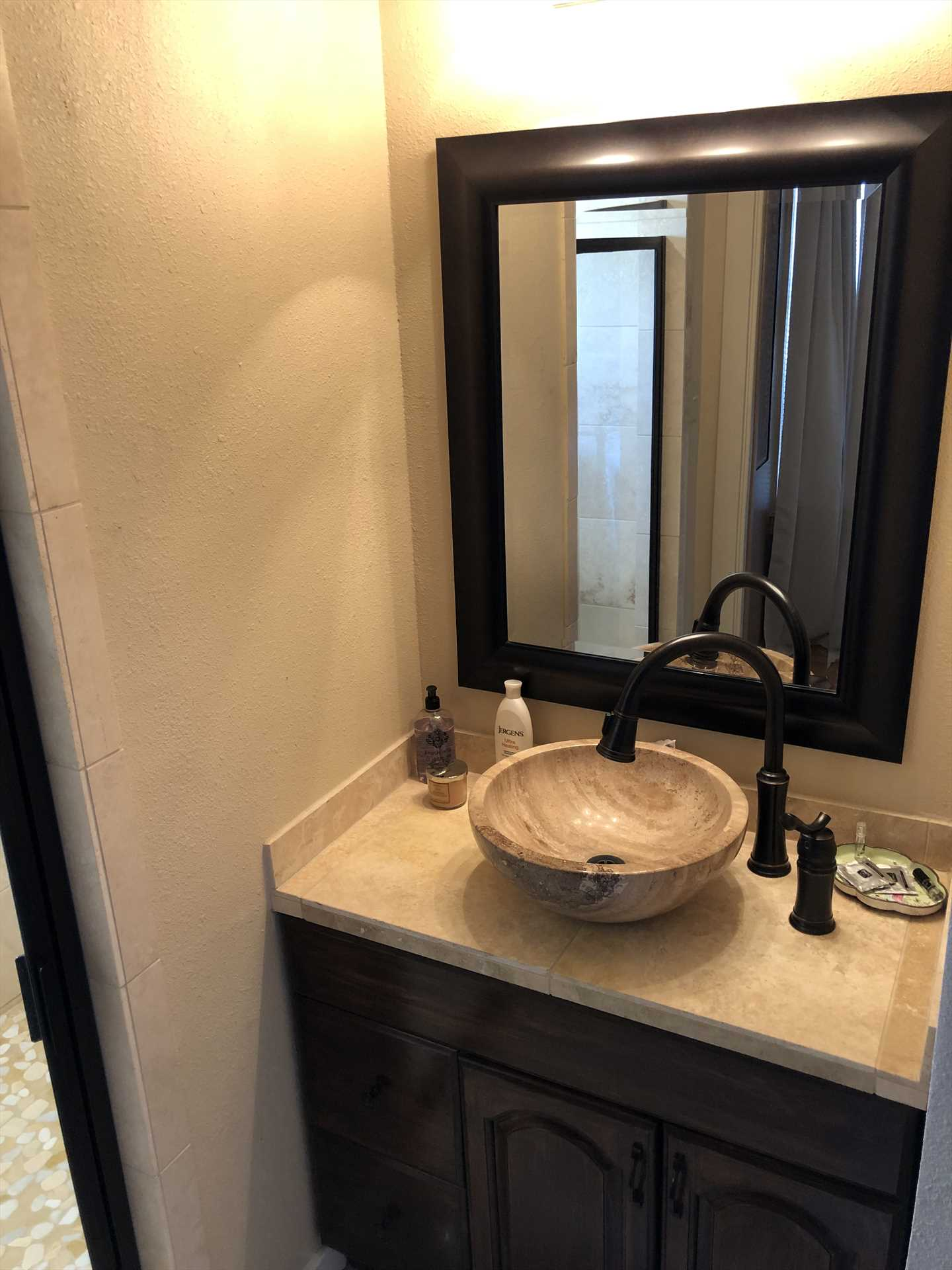 The boldly-framed vanity mirror over the bowl-style sink add style touches to the master bath, there's nothing ordinary about any room here!