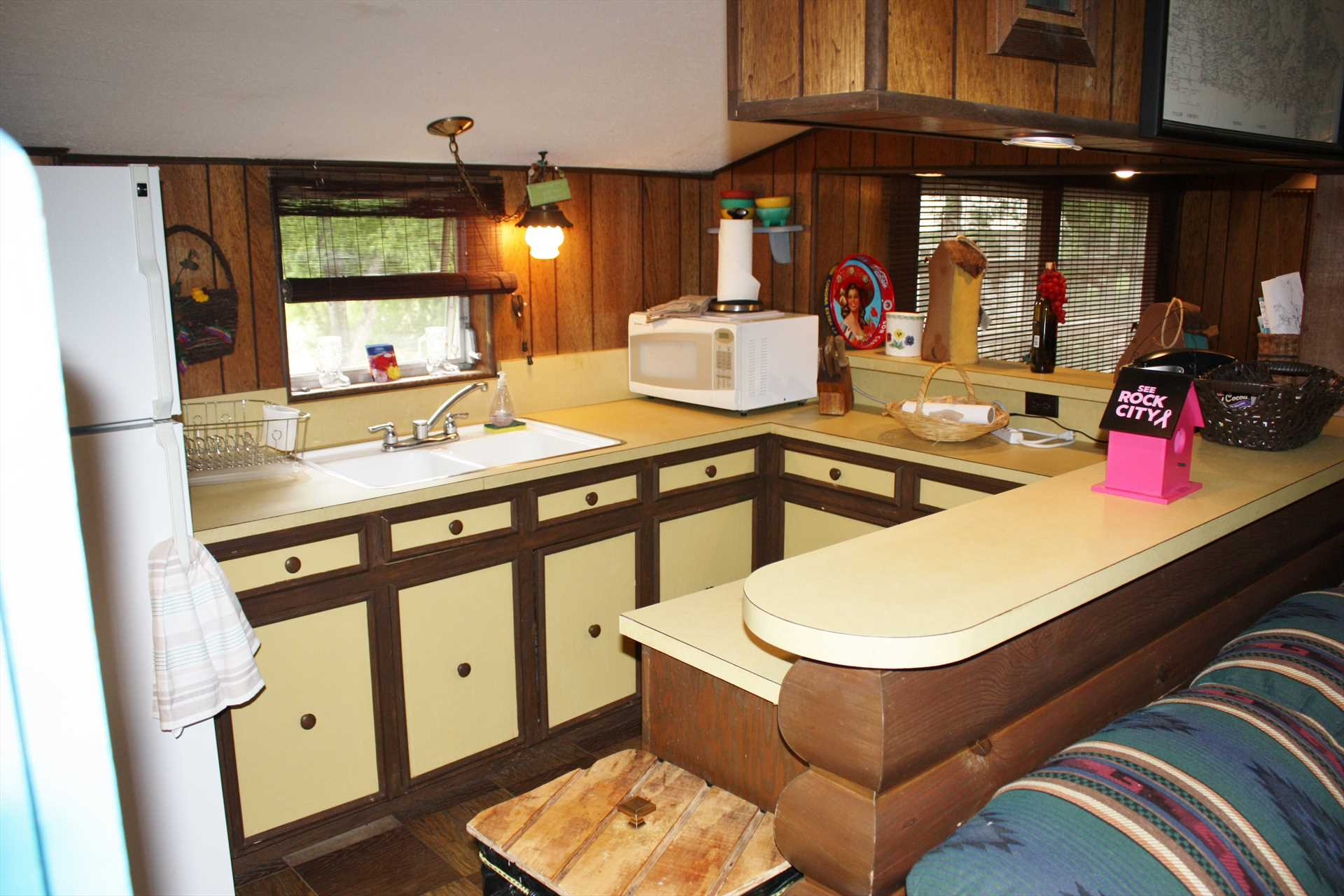 Fully decked out with appliances, the country kitchen also includes cooking ware, utensils, serving ware, dishes, and glasses.