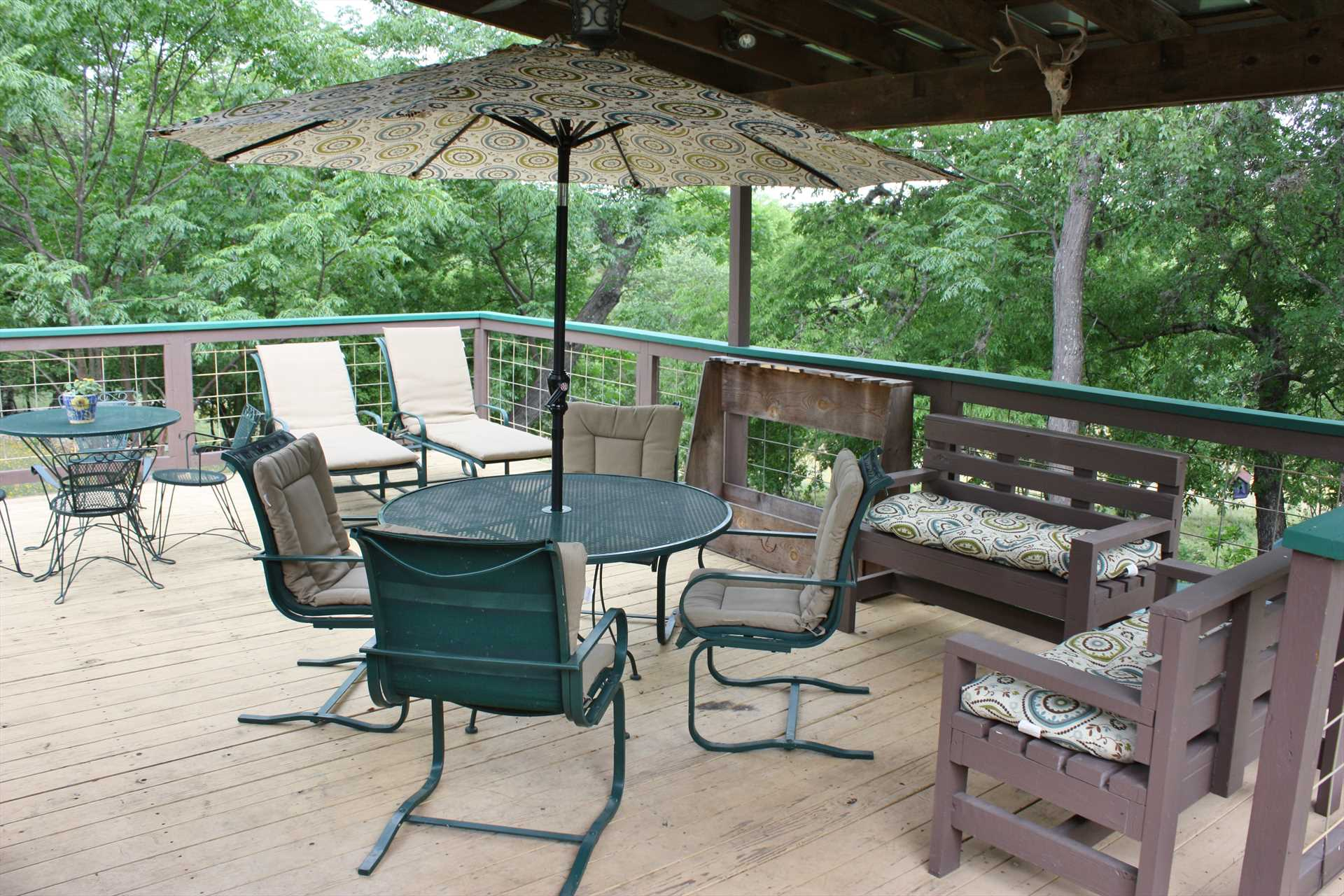 The half-shaded rear deck behind the main house has tons of comfortable outdoor furniture-and is a great perch for fantastic Hill Country views!