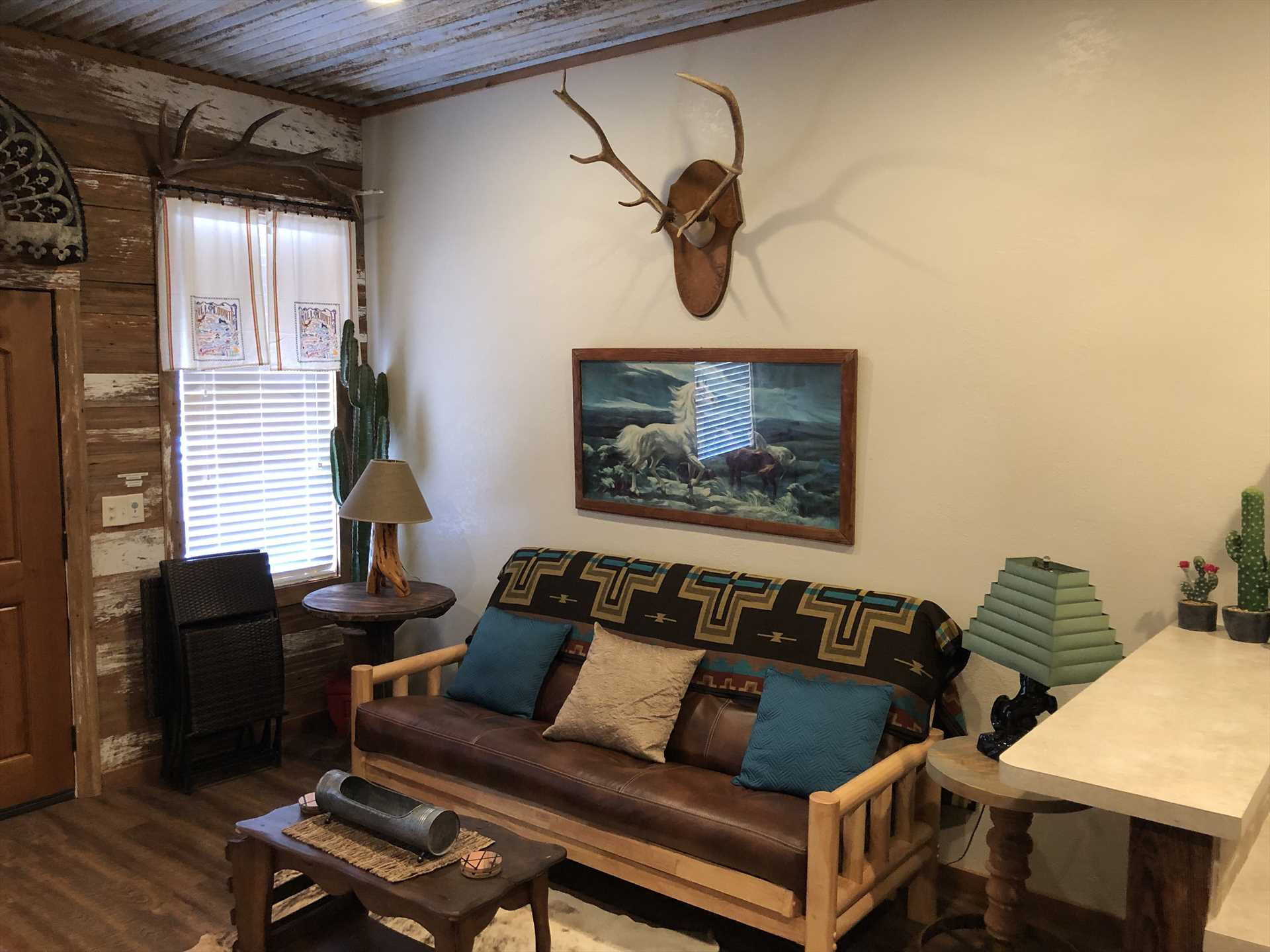 The welcoming western theme of the living area features a futon that also converts into a comfortable bed for two.