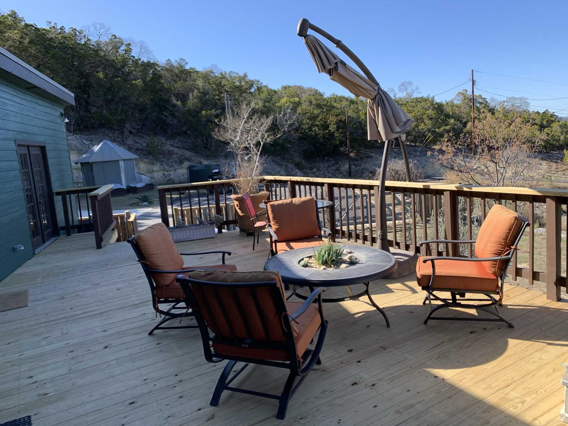 The deck features plenty of outdoor furniture, and a portable and adjustable source of shade.