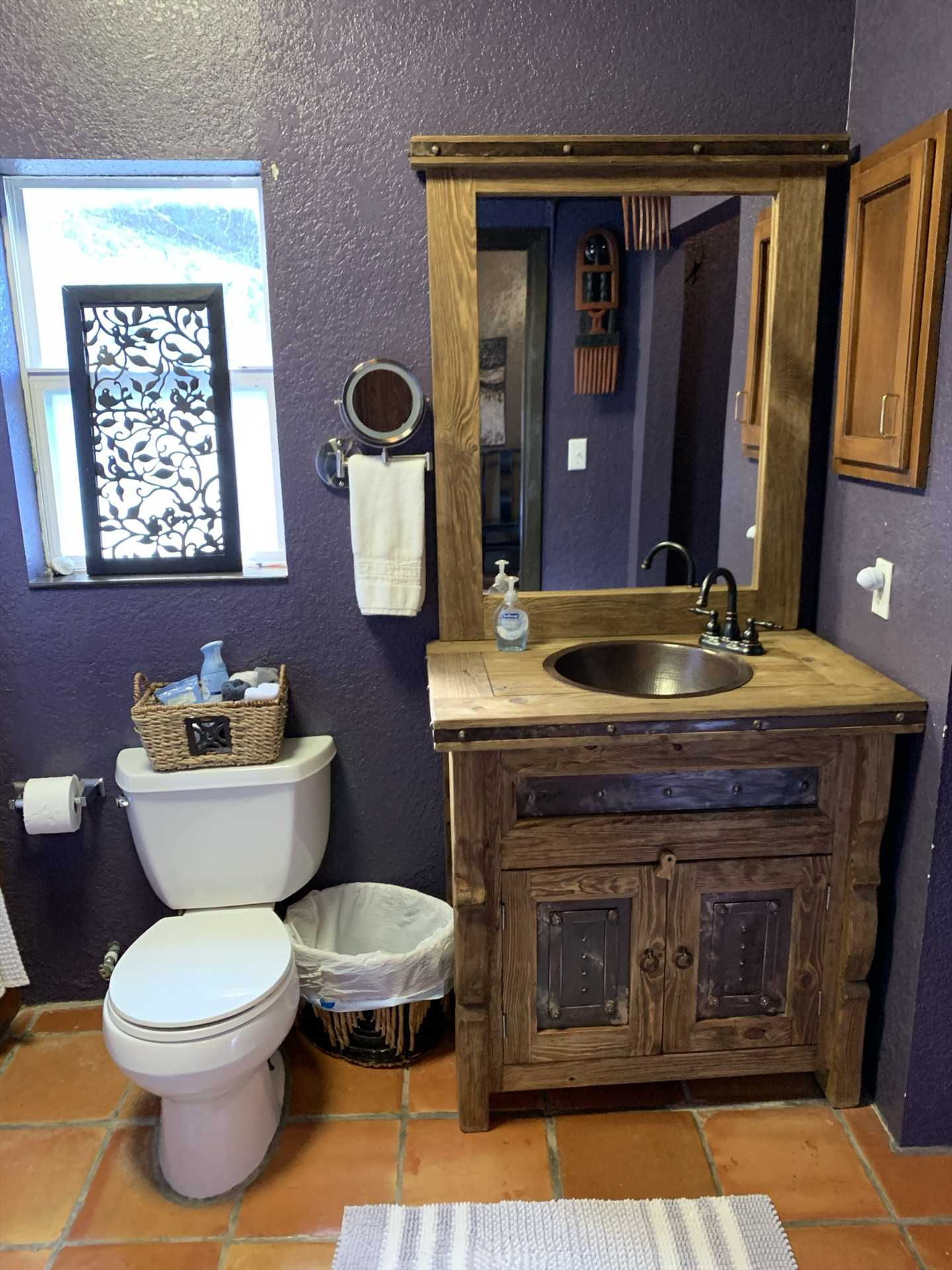 The stylish bathroom is stocked with select toiletries, a hair dryer, and even an iron and ironing board!