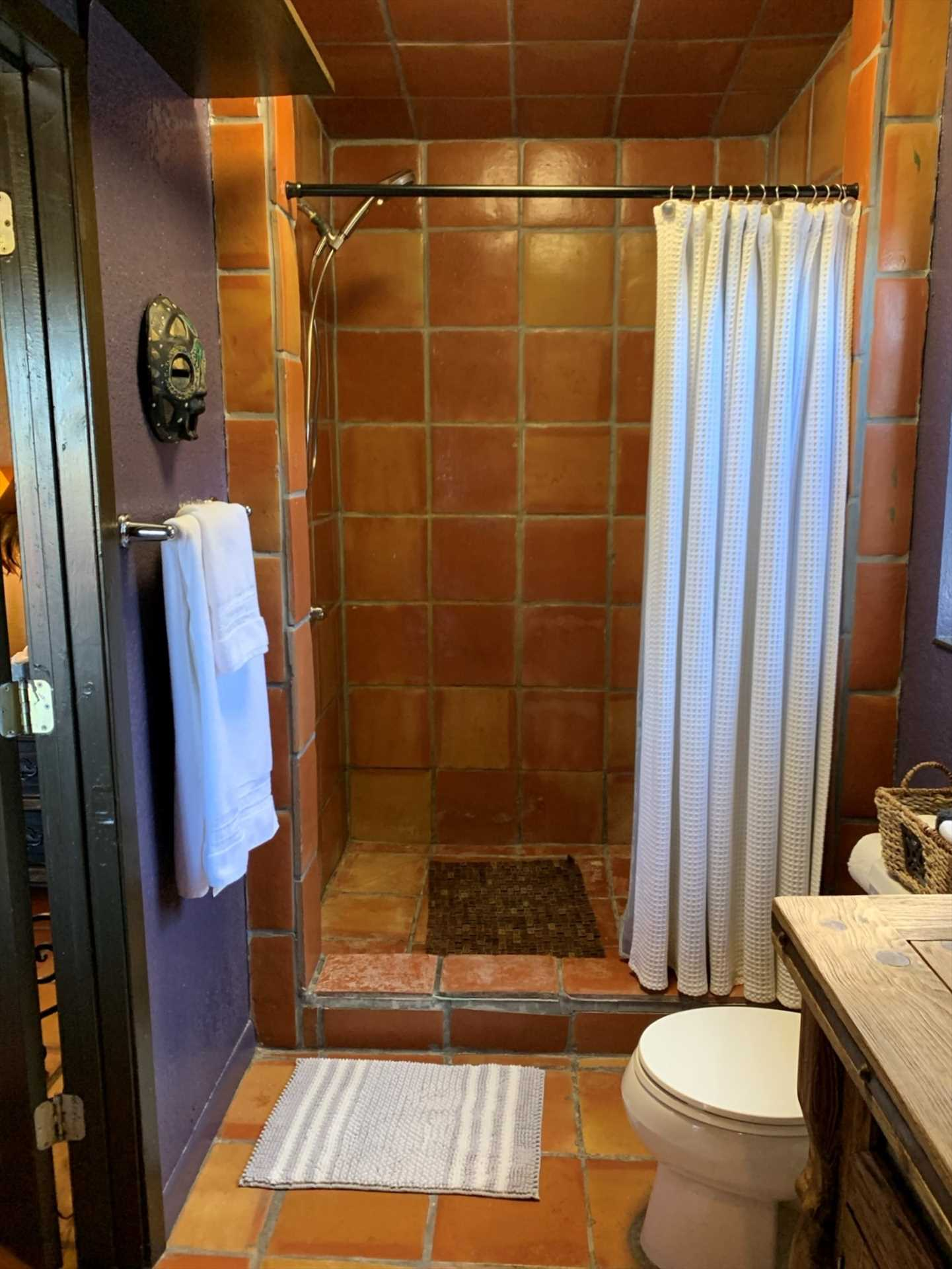 The full bath features a sit-down style shower with warm stone highlights-and all bed and bath linens are included for your stay.