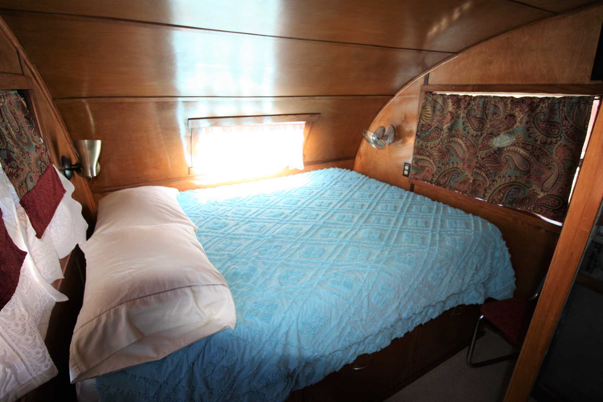 The private bedroom includes a comfy queen-sized bed! Clean bed linens are provided for your stay in this lovingly-refurbished Spartanette trailer coach.