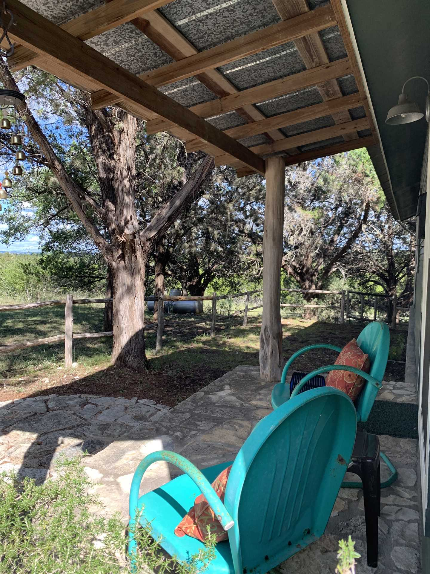 Savor a quiet moment on the shaded porch that overlooks the tree-lined property.