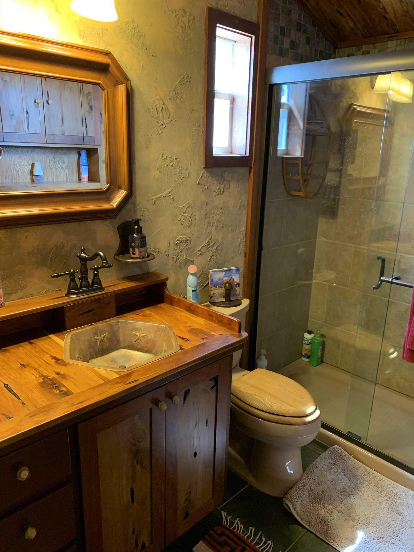The full bath features a shower stall, unique wood-accented vanity, and plenty of fluffy and clean linens.