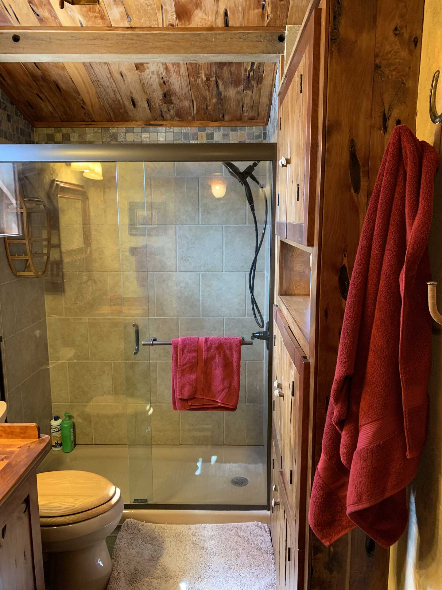 The warm, wood-highlighted theme of the cabin continues in the full bath, which ix kept neat as a pin.