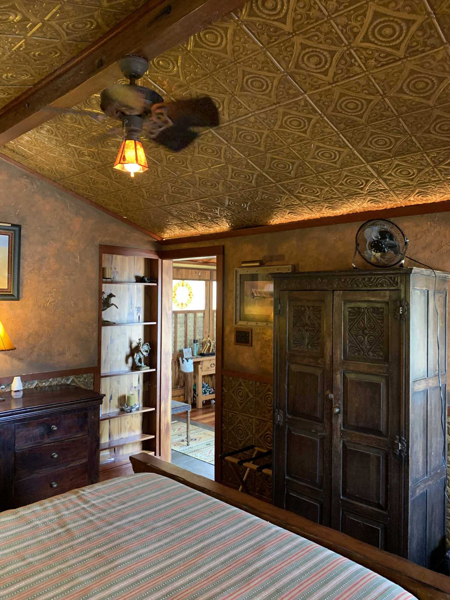 The delightful vintage decor continues in the bedroom, which is accented by charming tin panels and a beamed ceiling!