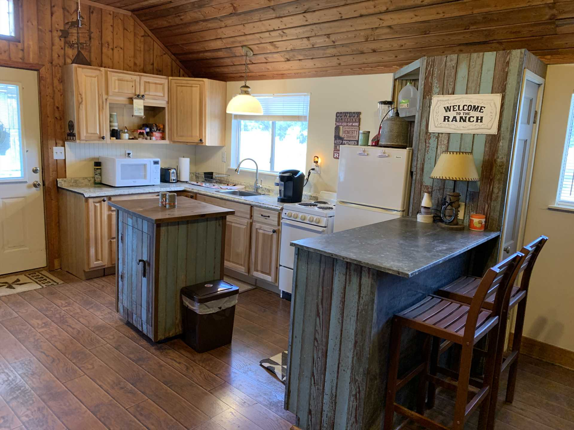 Appliances, utensils, and coffee fixin's are all included in the tidy country kitchen.
