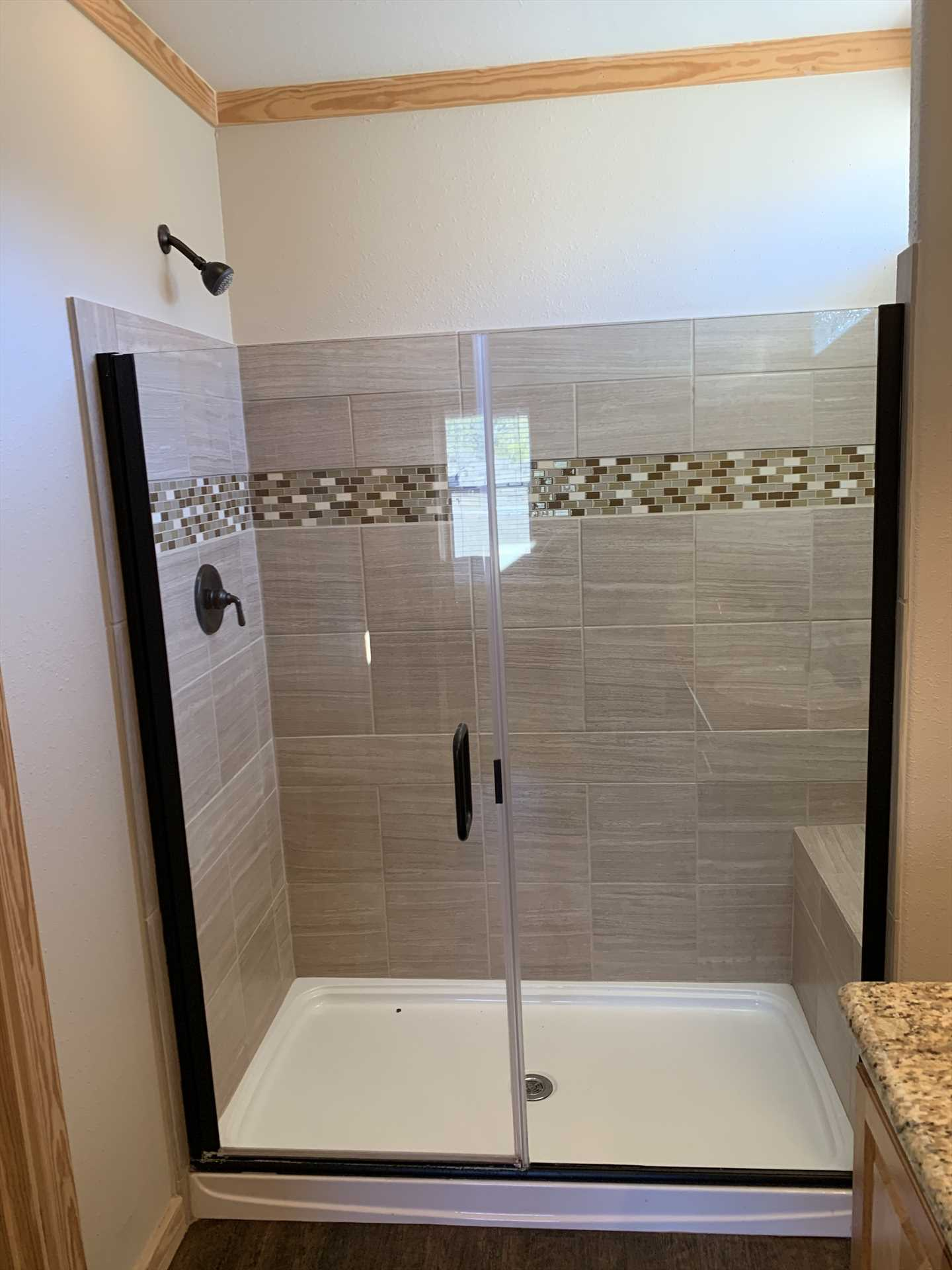 Beautiful tile accents in the master shower add pretty highlights to your roomy cleanup space.