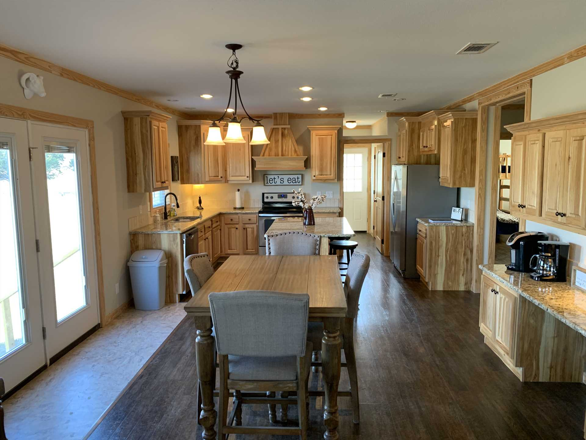 Marbleized counters and blond wood cabinets in the kitchen and dining area shine nicely in warm natural light during the day.