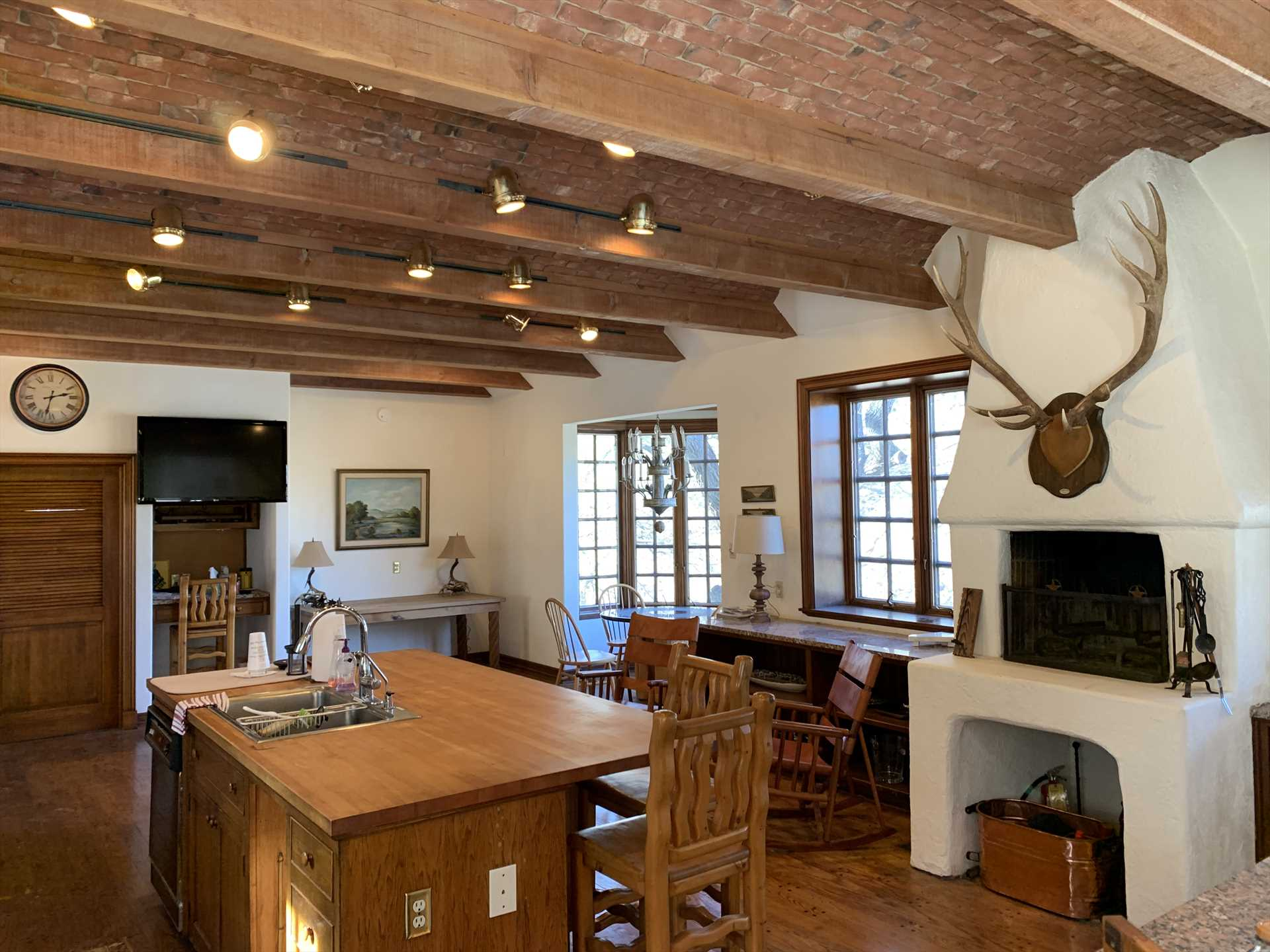 Beamed ceilings and track lighting add stylish and functional touches in the gathering area near the Homestead's kitchen, which is equipped with all the appliances, cookware, and serving ware you'll need.