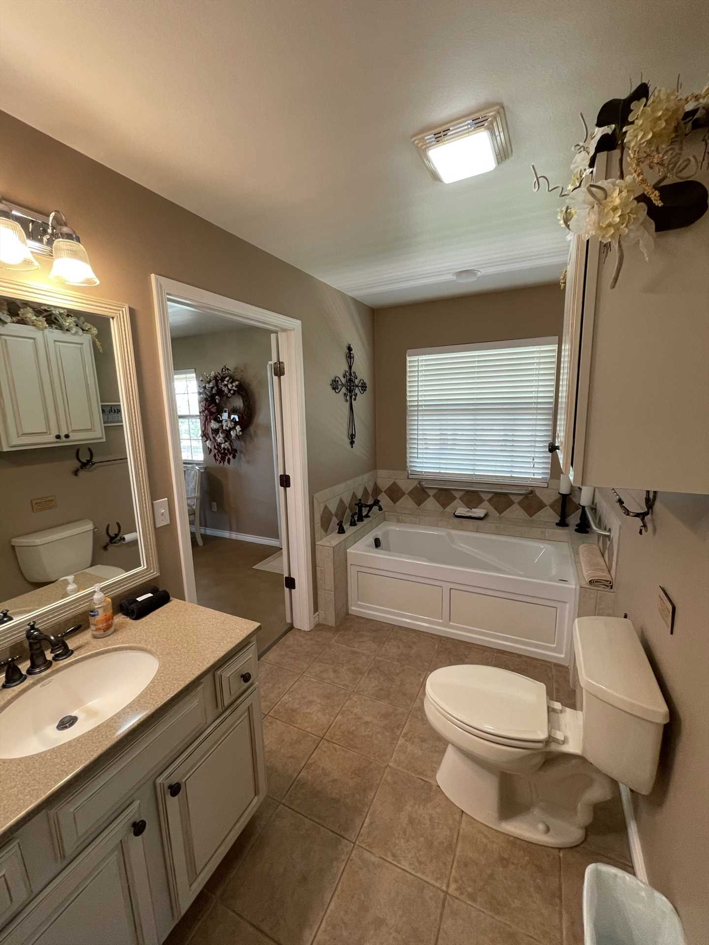 This immaculately clean bathroom features a roomy tub to soak in, and a vanity with plenty of counter space. Clean bath linens are included as part of your stay!