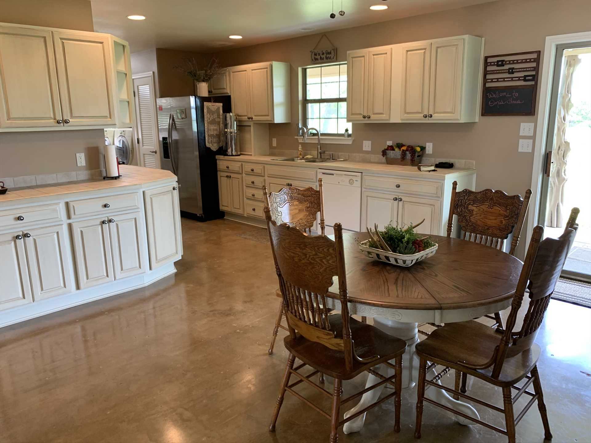 Clean white cabinets, natural light, and vintage furnishings create a fresh and vibrant atmosphere in the kitchen and dining area.