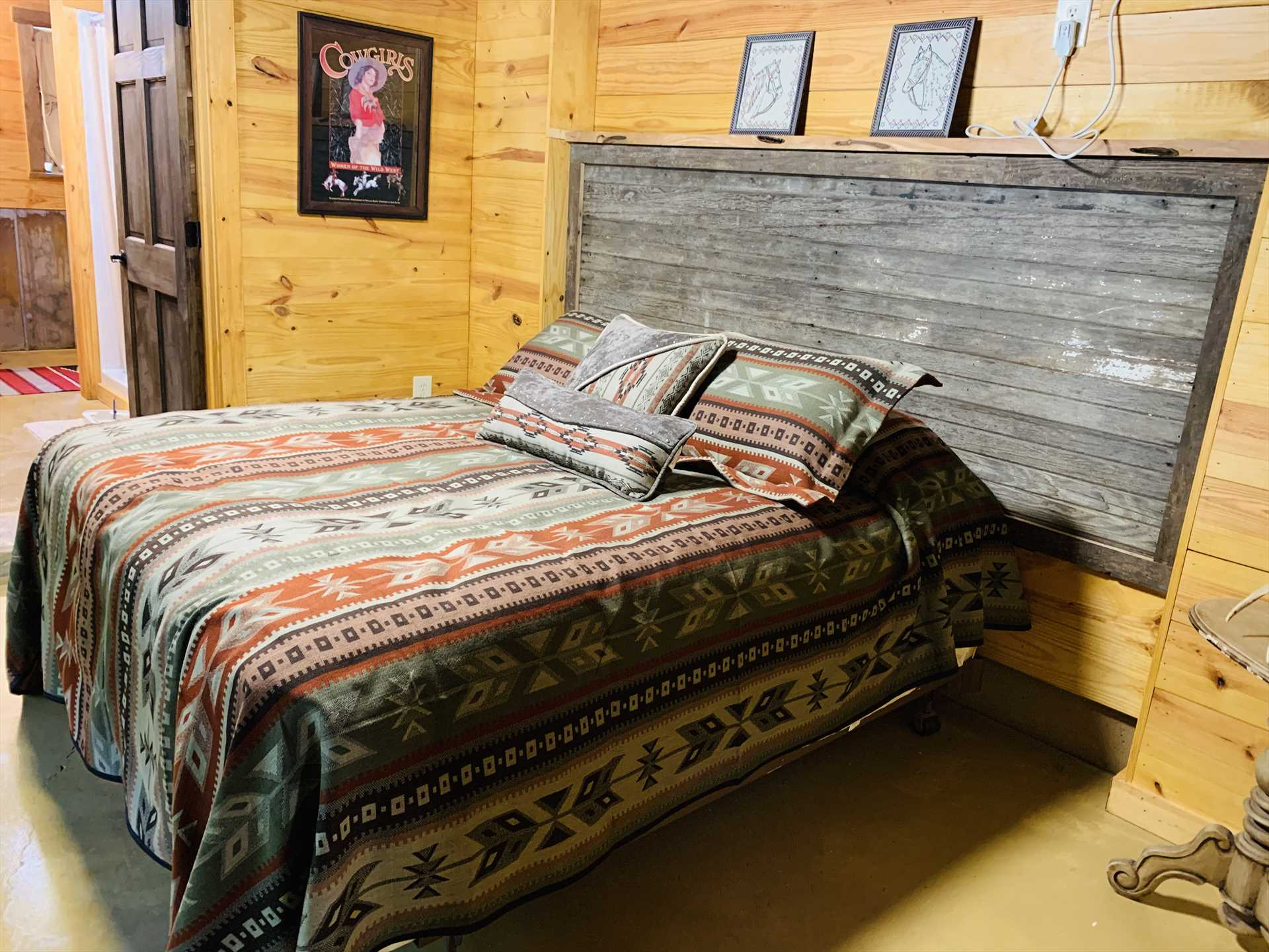 The plush queen-sized bed comes with soft and comfy linens-and check out that barn board headboard!