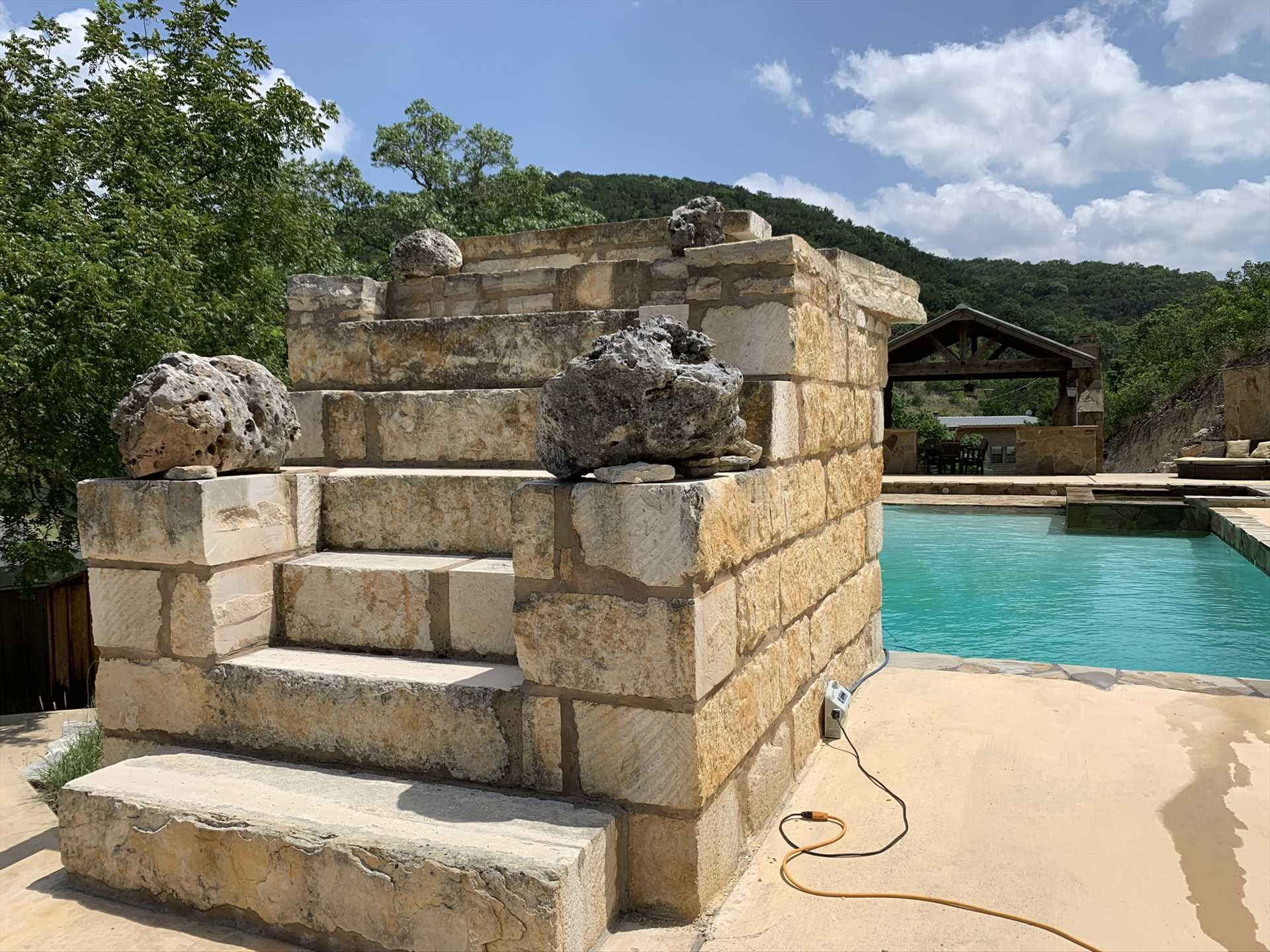 Take the plunge! This custom stone diving platform is your launching spot into the cool and crystal-clear waters of the pool.