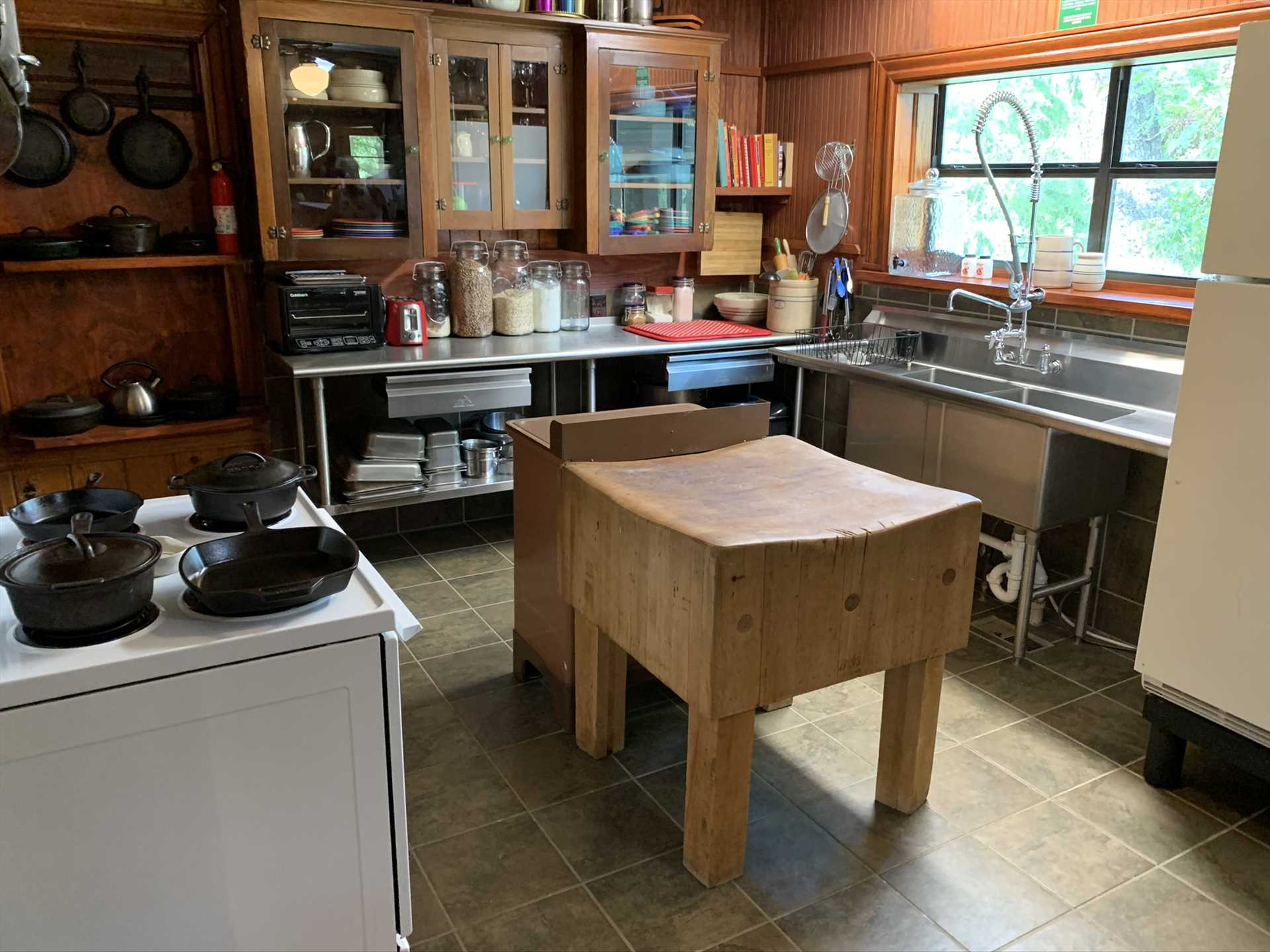 Equipped with modern appliances, a butcher block, and industrial sink, the commercial-grade kitchen is a fantastic place for culinary artists to strut their stuff!