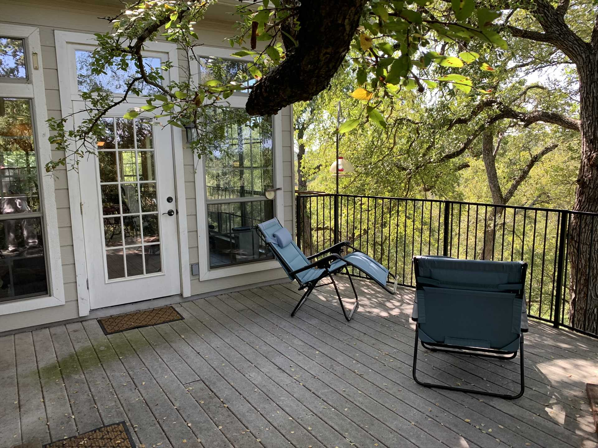 The tree-shaded patio is located up high, for stunning views! Kids and pets are protected on the patio by sturdy fencing. Please note that the path down to the river from here can be steep and occasionally slippery.
