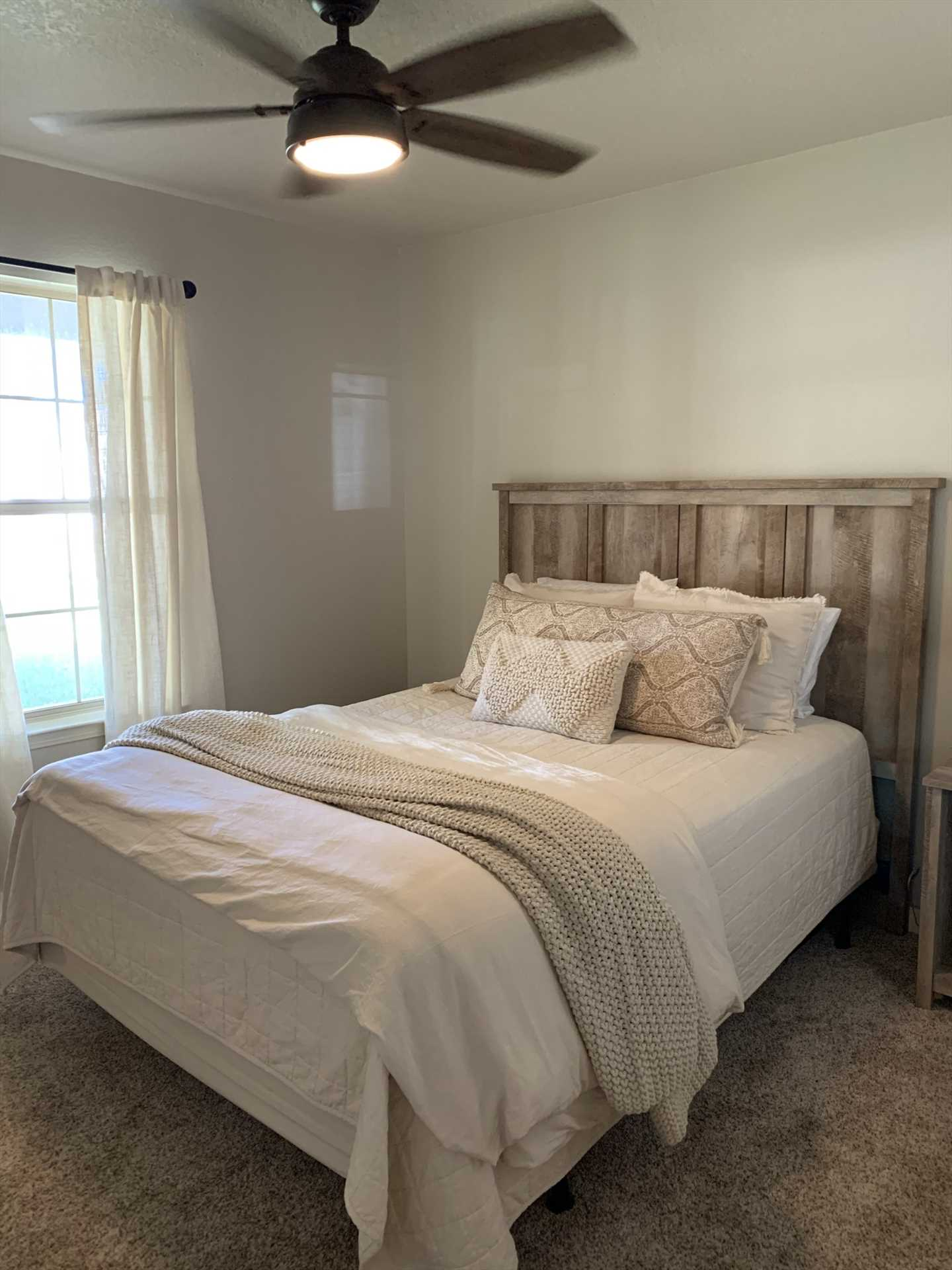 A clean and stylish queen-sized bed graces the second bedroom, and all three bedrooms here are appointed with fresh and soft bed linens.