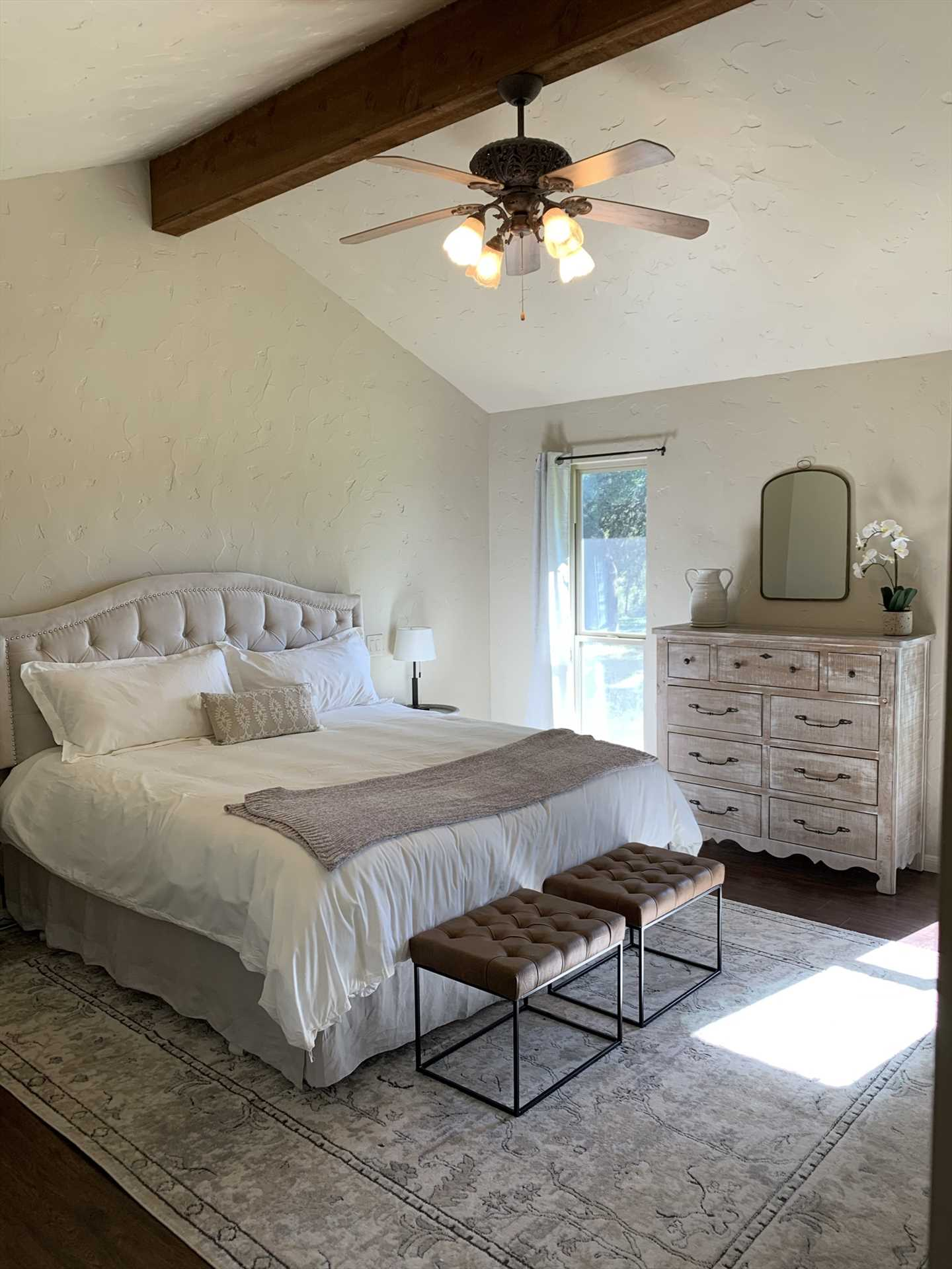 A high beamed ceiling and enormous king-sized bed provide royal accommodations for two in the master bedroom.