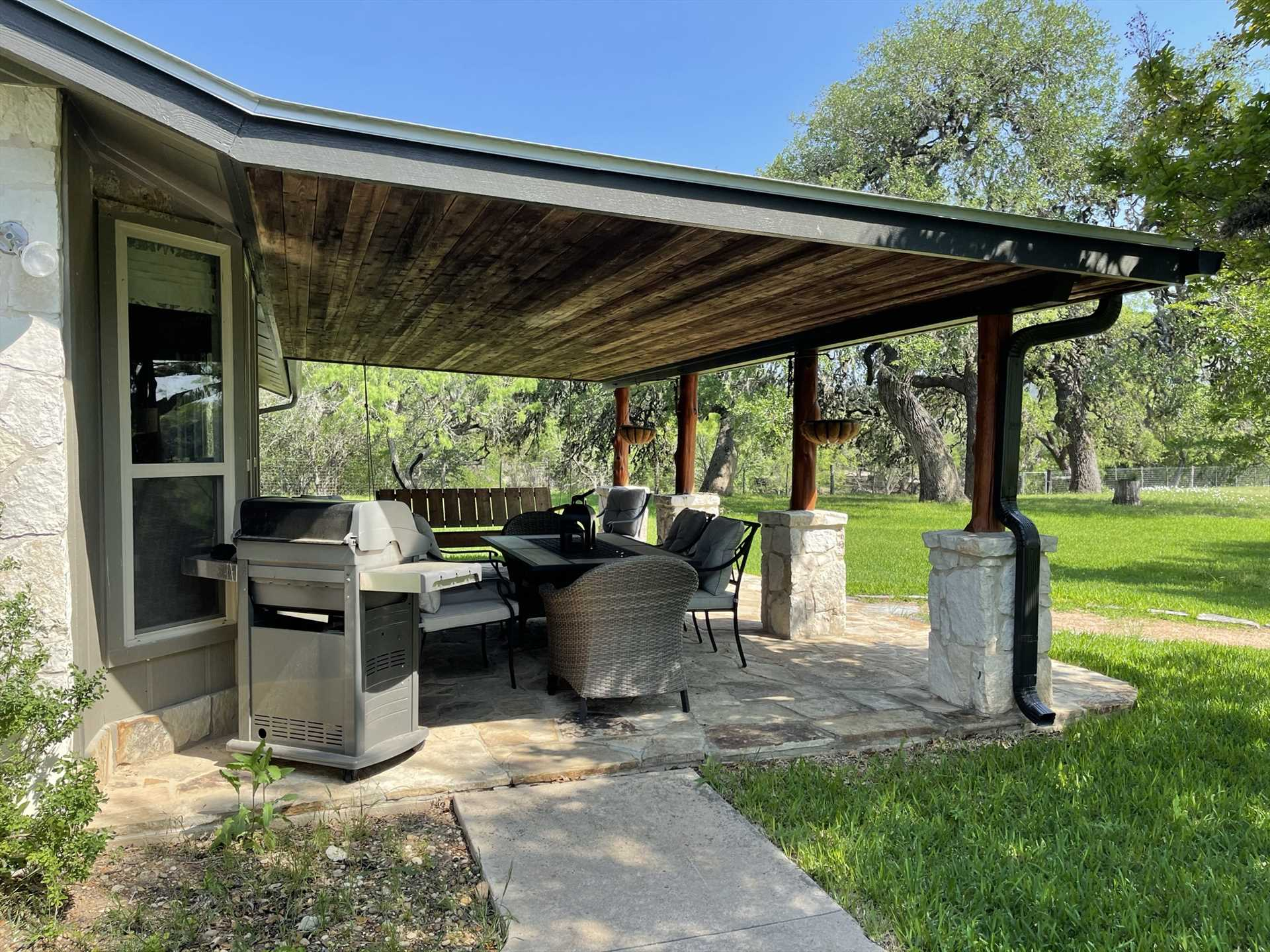 Unique stone-and-tree-trunk pillars support the shaded cover for the patio, a rustic and comfortable place to enjoy the Hill Country.