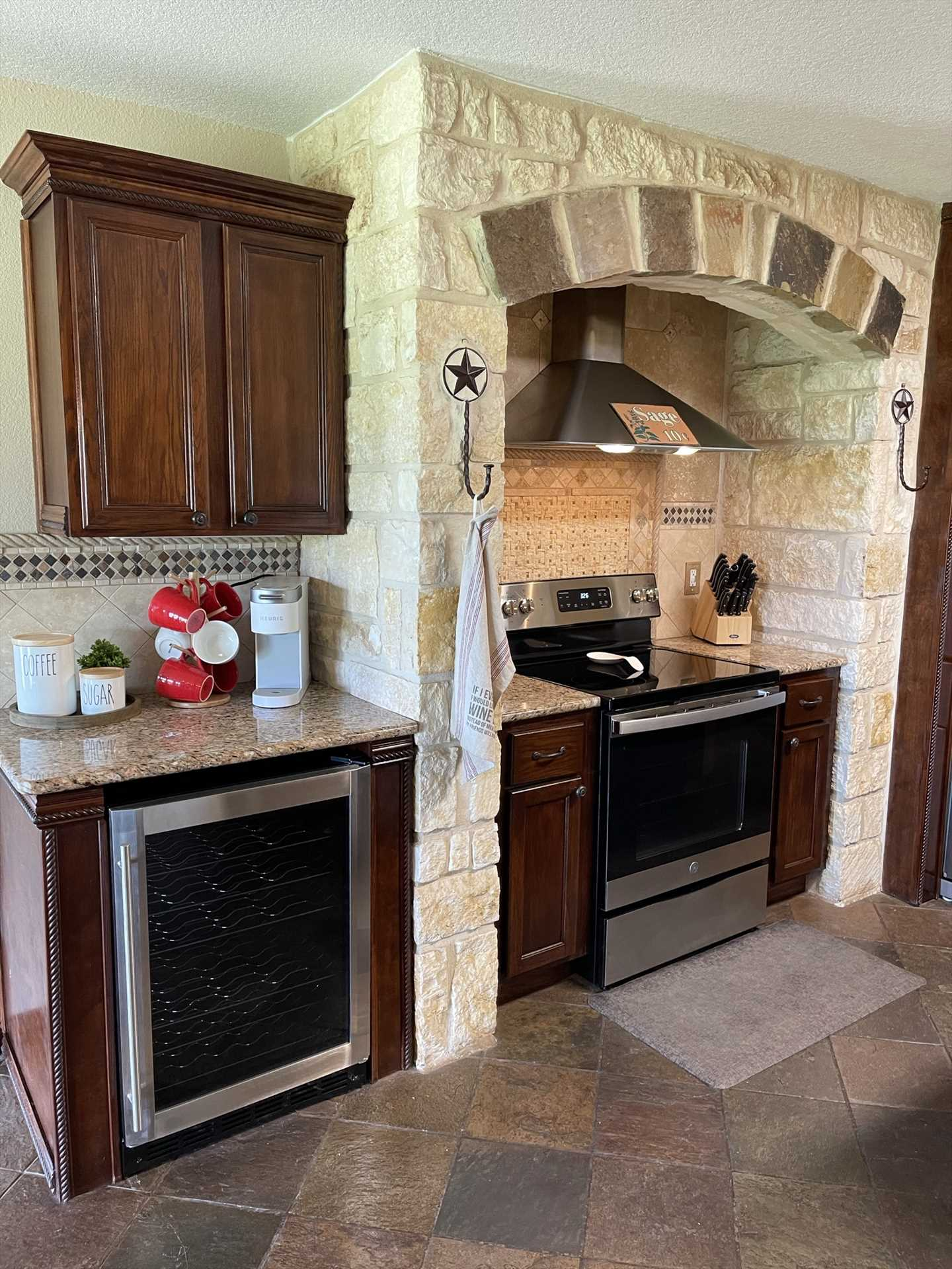 The well-appointed kitchen features not only modern appliances, but pretty and functional wood and stone highlights.