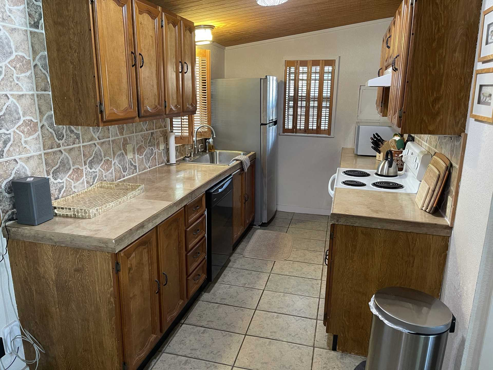 Pots, pans, cutlery, serving ware, glasses, and a full complement of appliances make the kitchen a cook's delight.