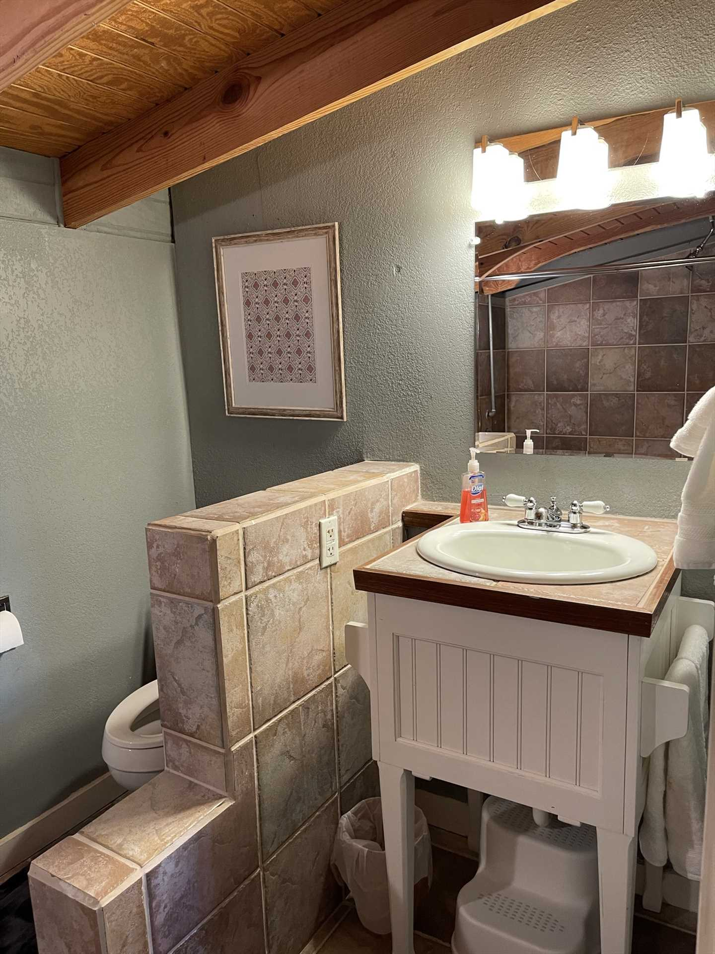 Next to the vanity in the second bathroom, you'll find a convenient half-wall where you can keep your toiletries!