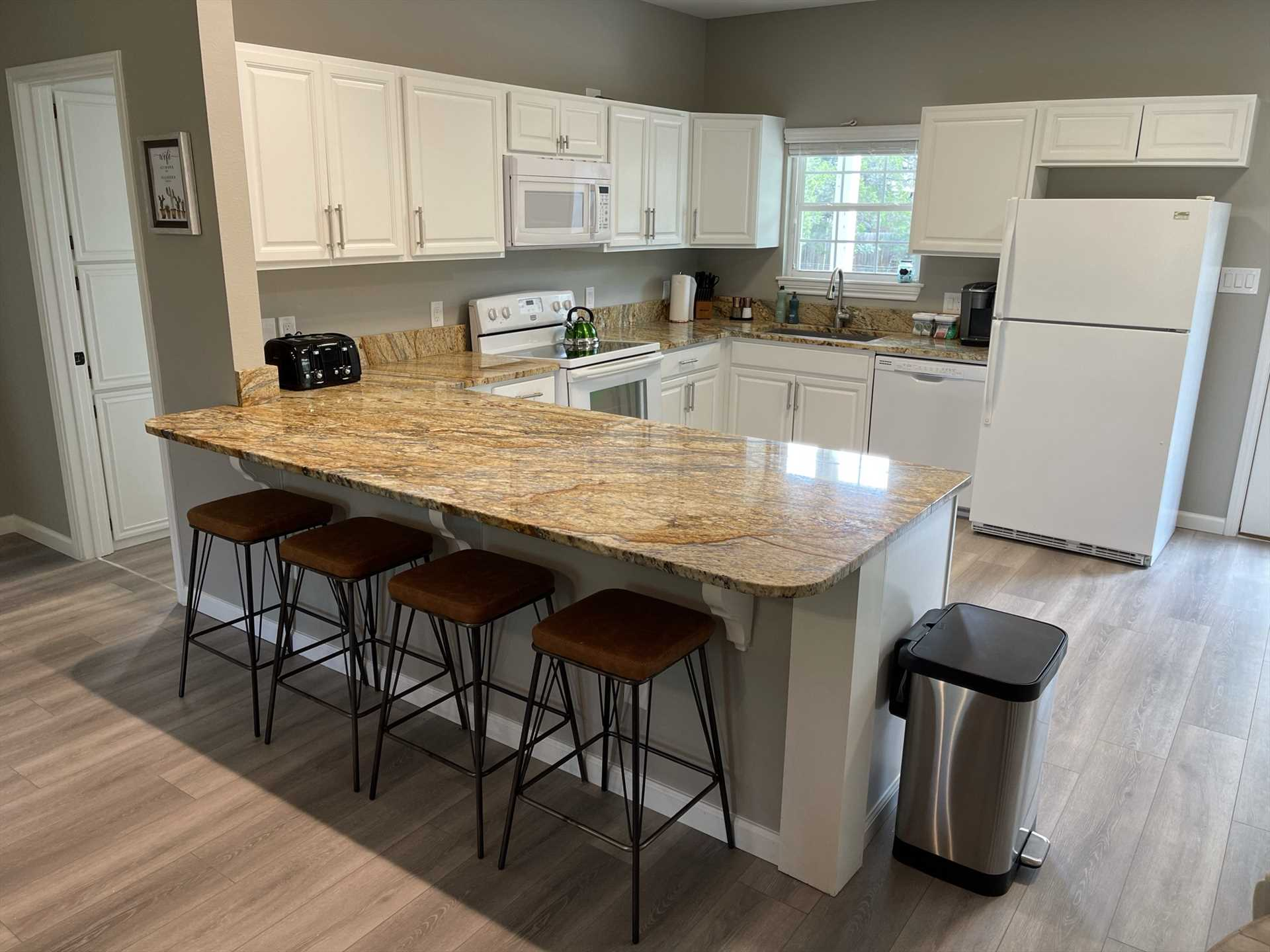 The modern kitchen features all the appliances, cookware, and serving ware you'll need, tons of counter space, and even bar seating so folks can chat while prepping meals.