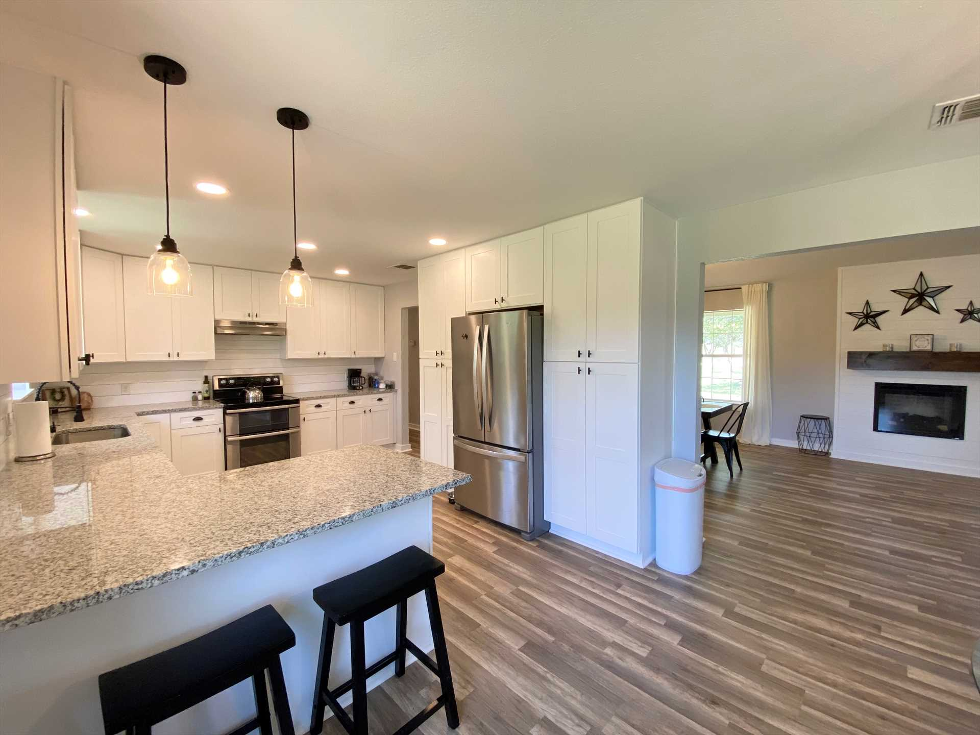 With a wide-open floor plan, the centrally-located fireplace radiates warmth all throughout the living area, dining area, and kitchen.