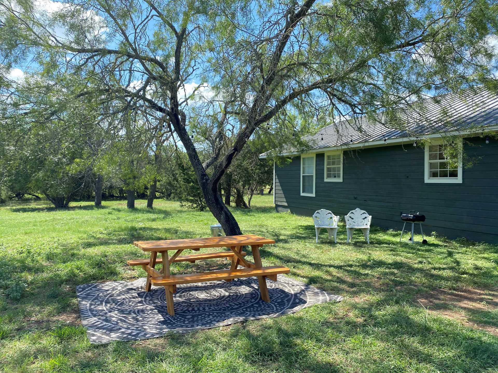 The shaded picnic table is the perfect place to sample a nice BBQ spread you've prepared on the charcoal grill.