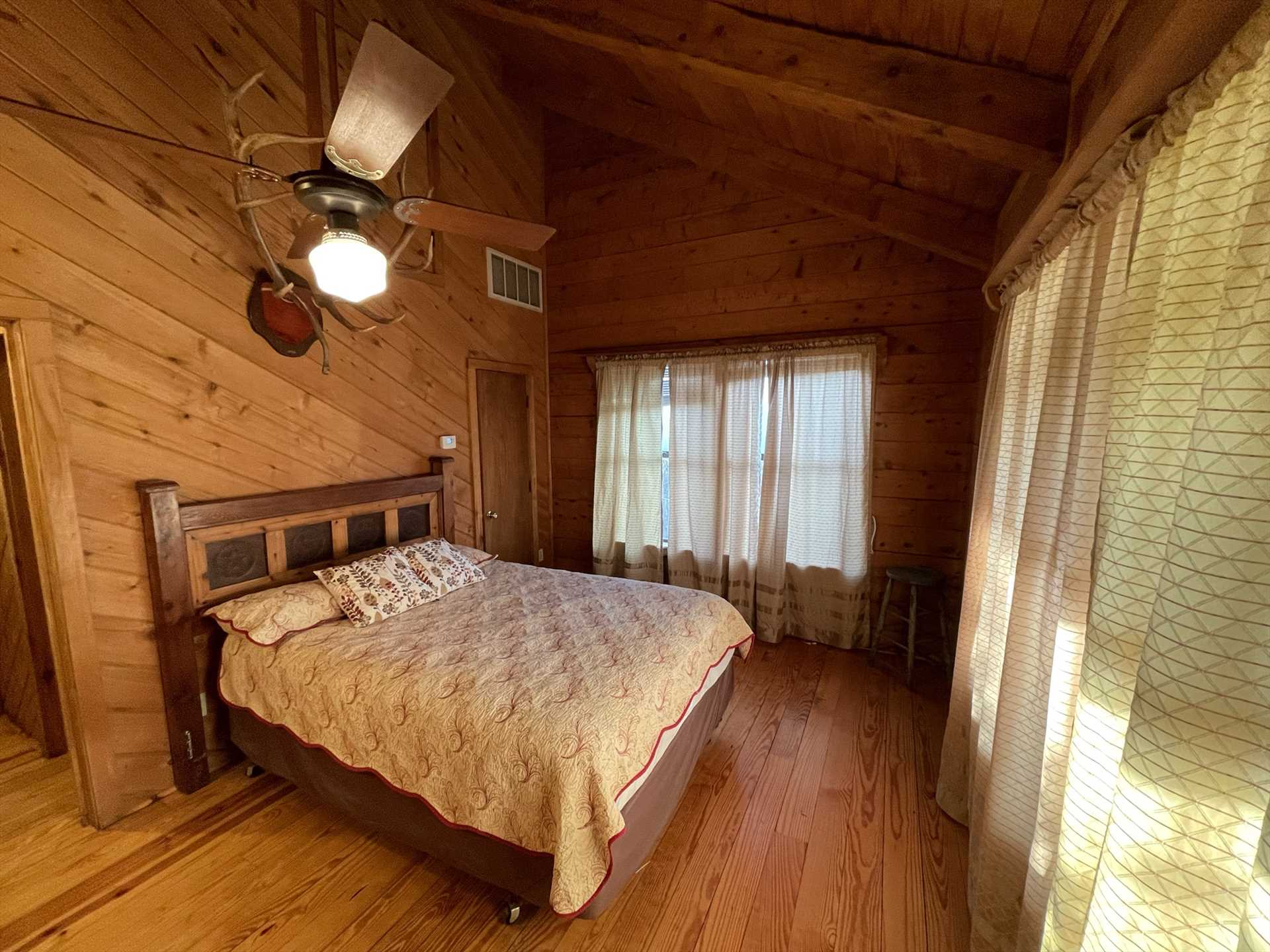 Rest and recharge in the second bedroom, stylishly paneled and decorated, with a plush and comfy double bed.