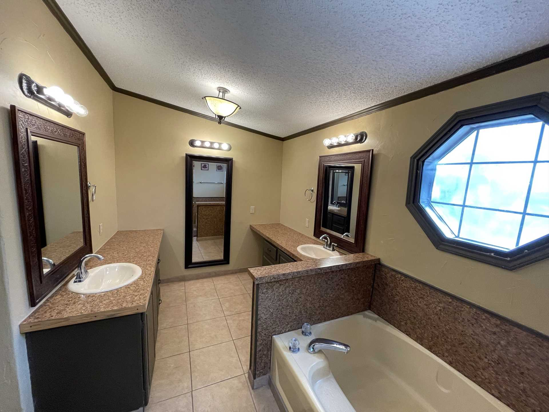Sharp and modern decor distinguishes the master bath, which includes a roomy tub and separate shower.