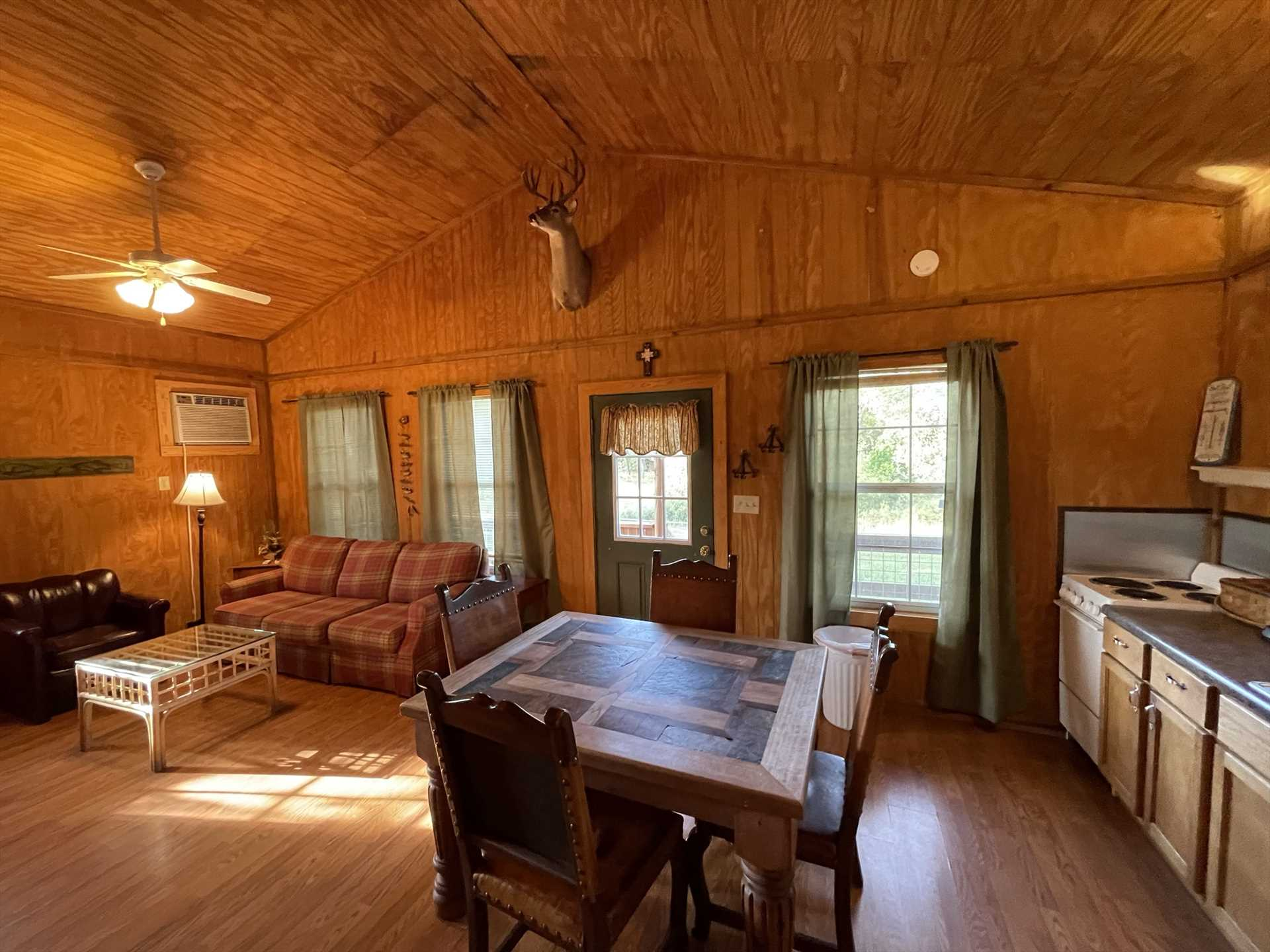 The main area of the Gone Fishin' cabin includes a full kitchen, dining table, and living space, all in a rustic and fun setting!