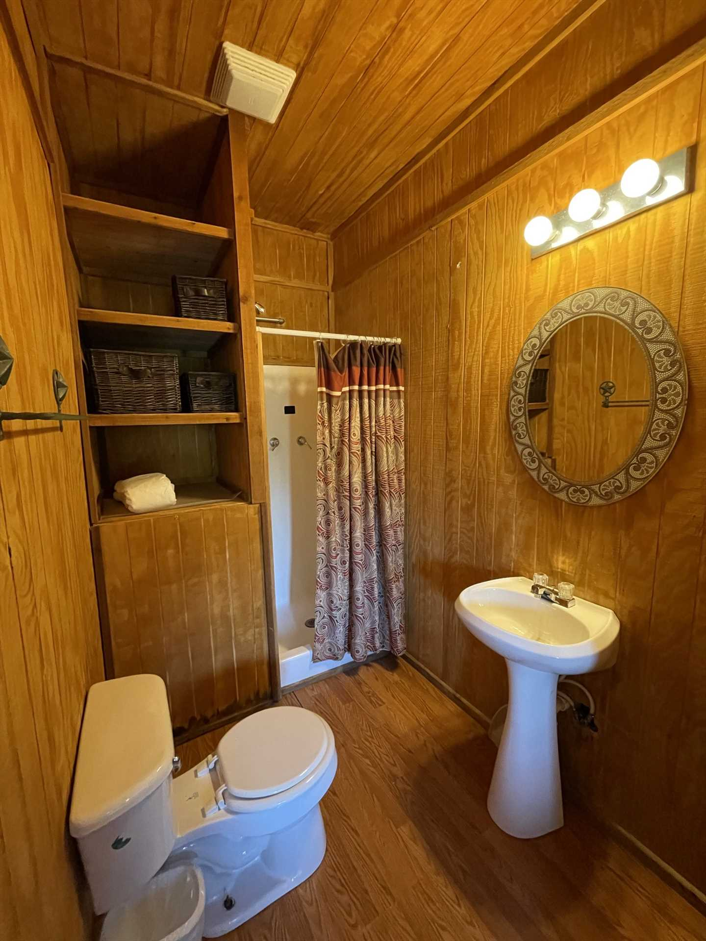 The full bath in the Gone Fishin' Cabin also features a clean shower stall and pedestal vanity.